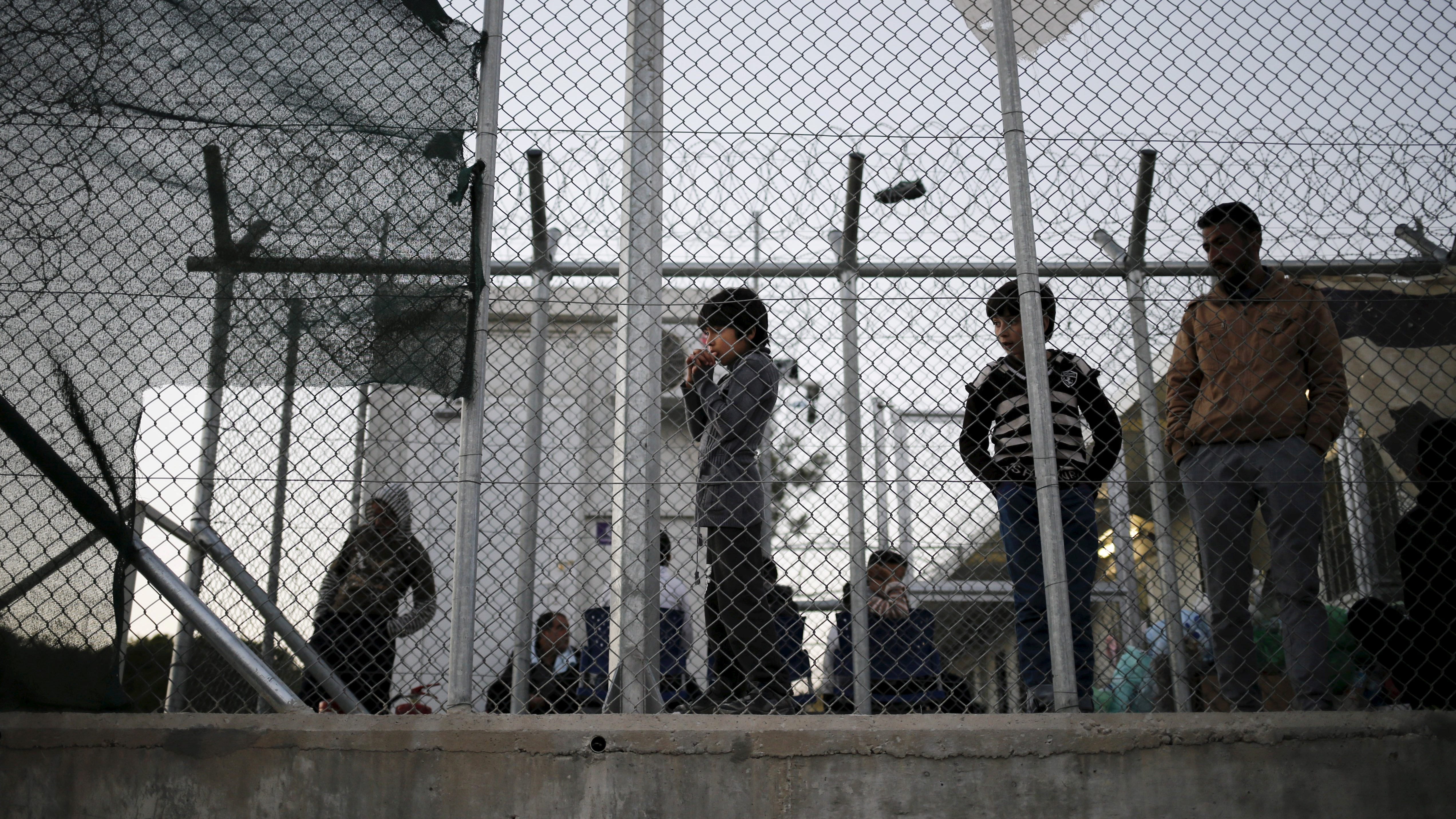 A migrant child stands next to a metal fence at the Moria refugee camp on the Greek island of Lesbos, November 5, 2015.