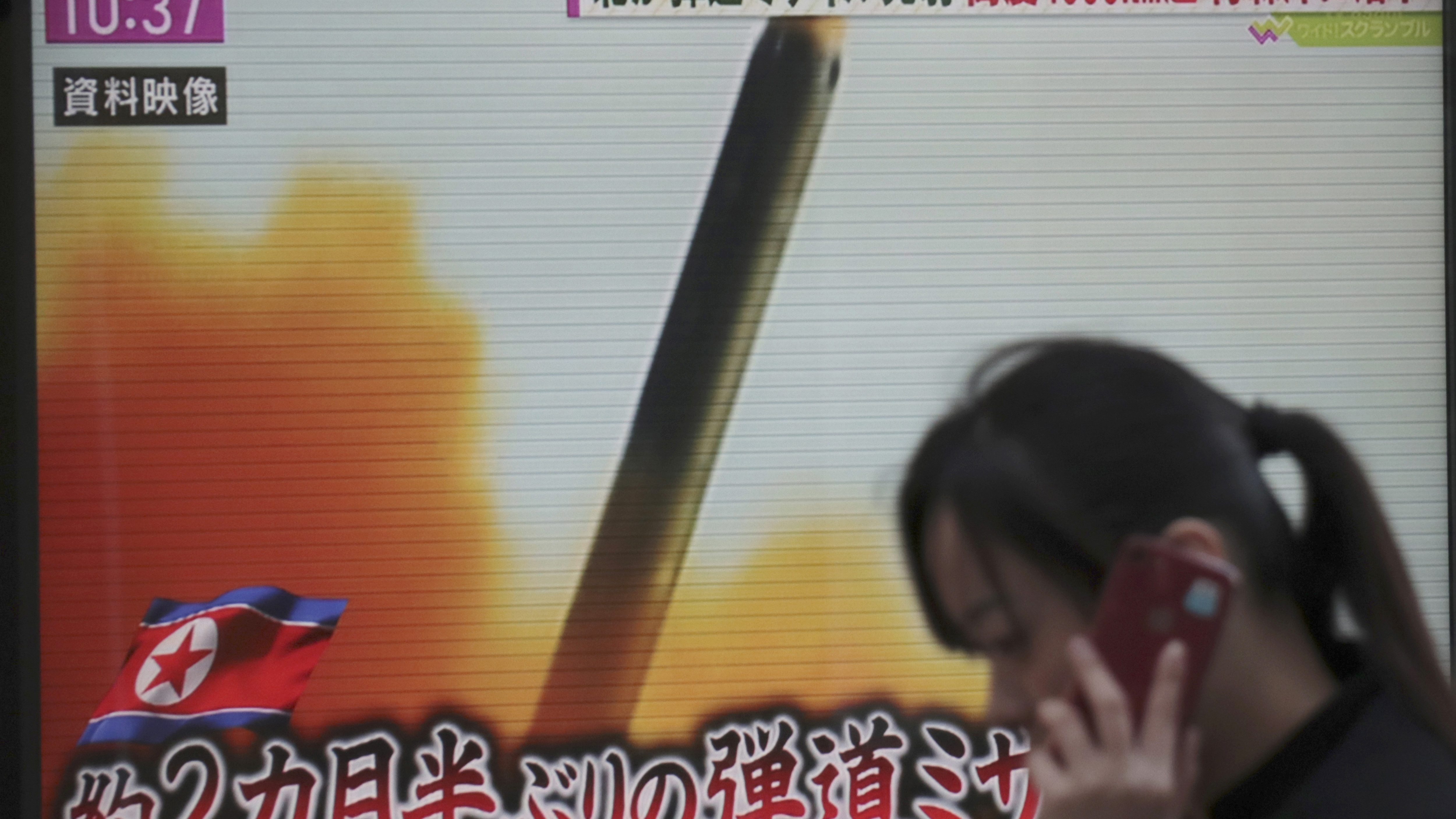 """A woman walks past a TV screen broadcasting news of North Korea's missile launch, in Tokyo, Wednesday, Nov. 29, 2017. After 2 ½ months of relative peace, North Korea launched its most powerful weapon yet early Wednesday, a presumed intercontinental ballistic missile that could put Washington and the entire eastern U.S. seaboard within range. The letters at bottom read """" Ballistic missile after 2 ½ months."""" (AP Photo/Shizuo Kambayashi)"""
