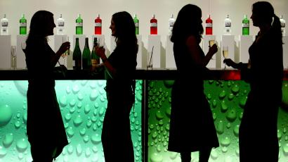 four women standing in front of a green bar.