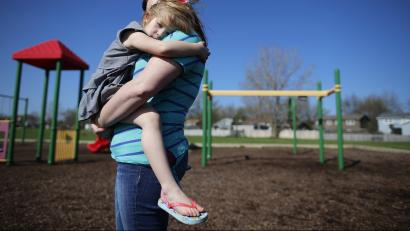 A woman holds her child in front of a playground