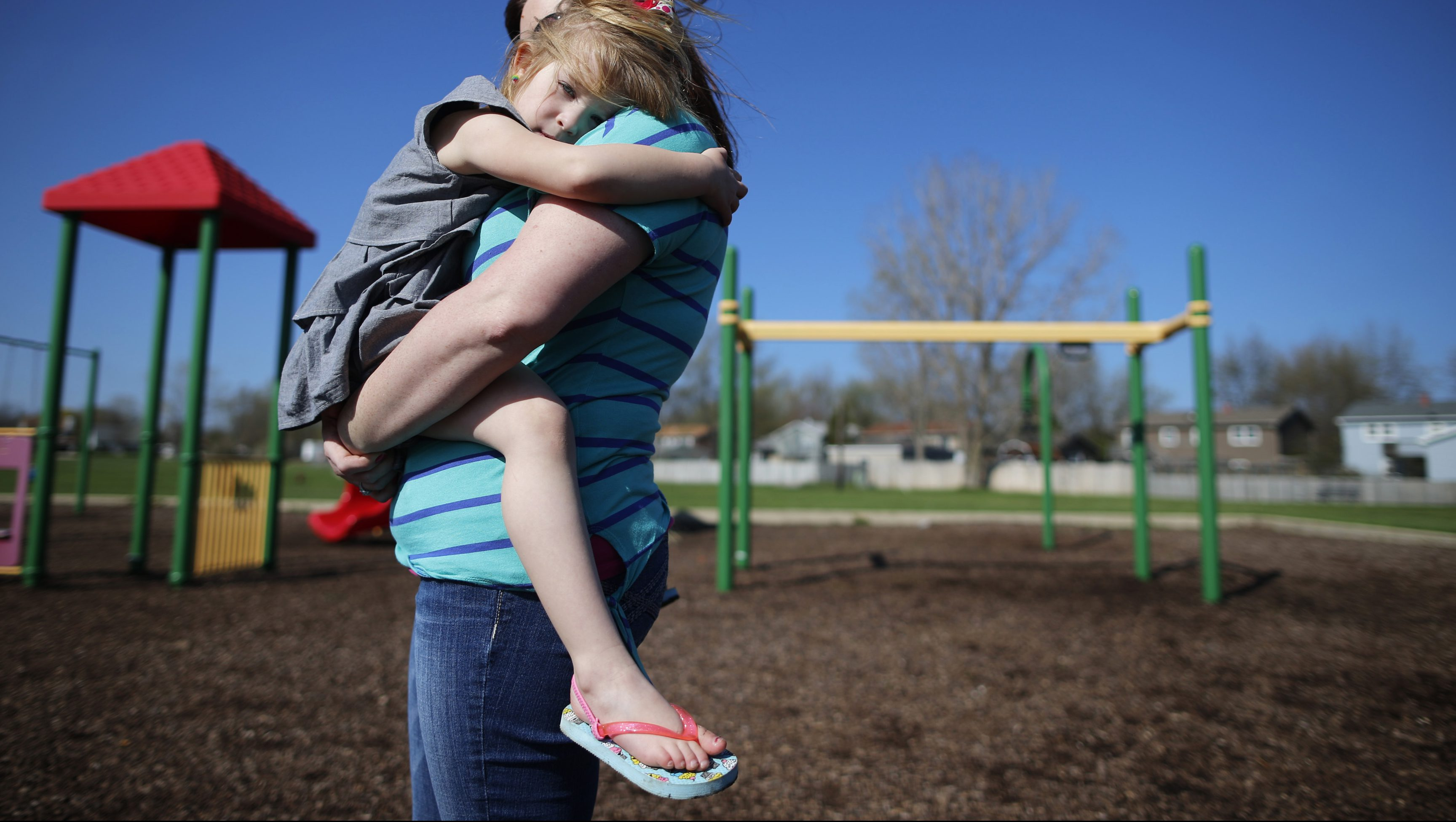 Andrea Smith holds her daughter Norah at a playground in Winthrop Harbor, Illinois, May 9, 2014.