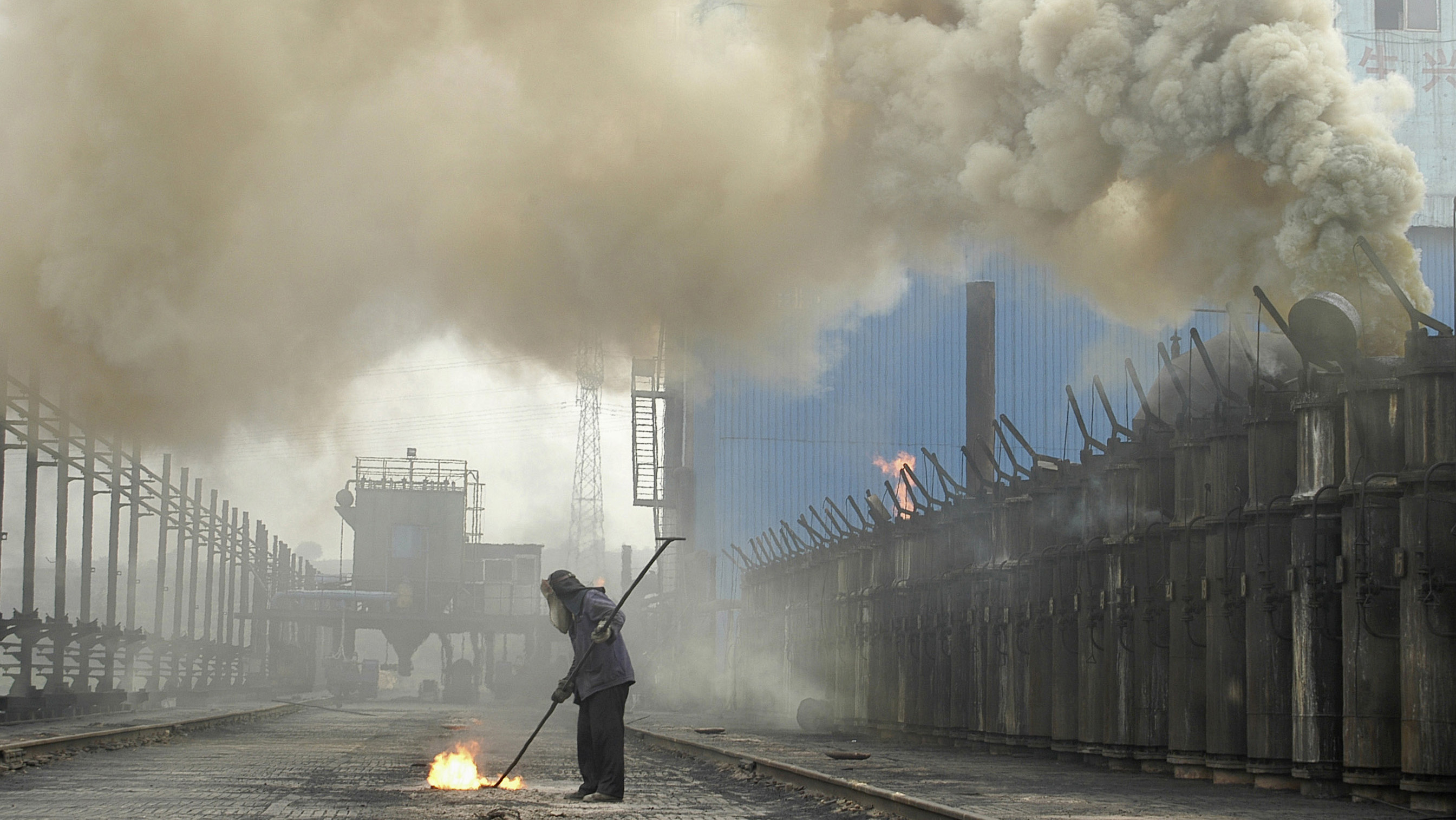 A labourer works at a coking plant in Changzhi, north China's Shanxi province, July 7, 2007. Starting off in Sydney on Saturday and travelling west around the world, the Live Earth concerts, planned for this weekend, are expected to attract more than a million people to raise awareness of global warming and environmental issues like climate change. REUTERS/Stringer (CHINA) CHINA OUT - GM1DVQNFJGAA