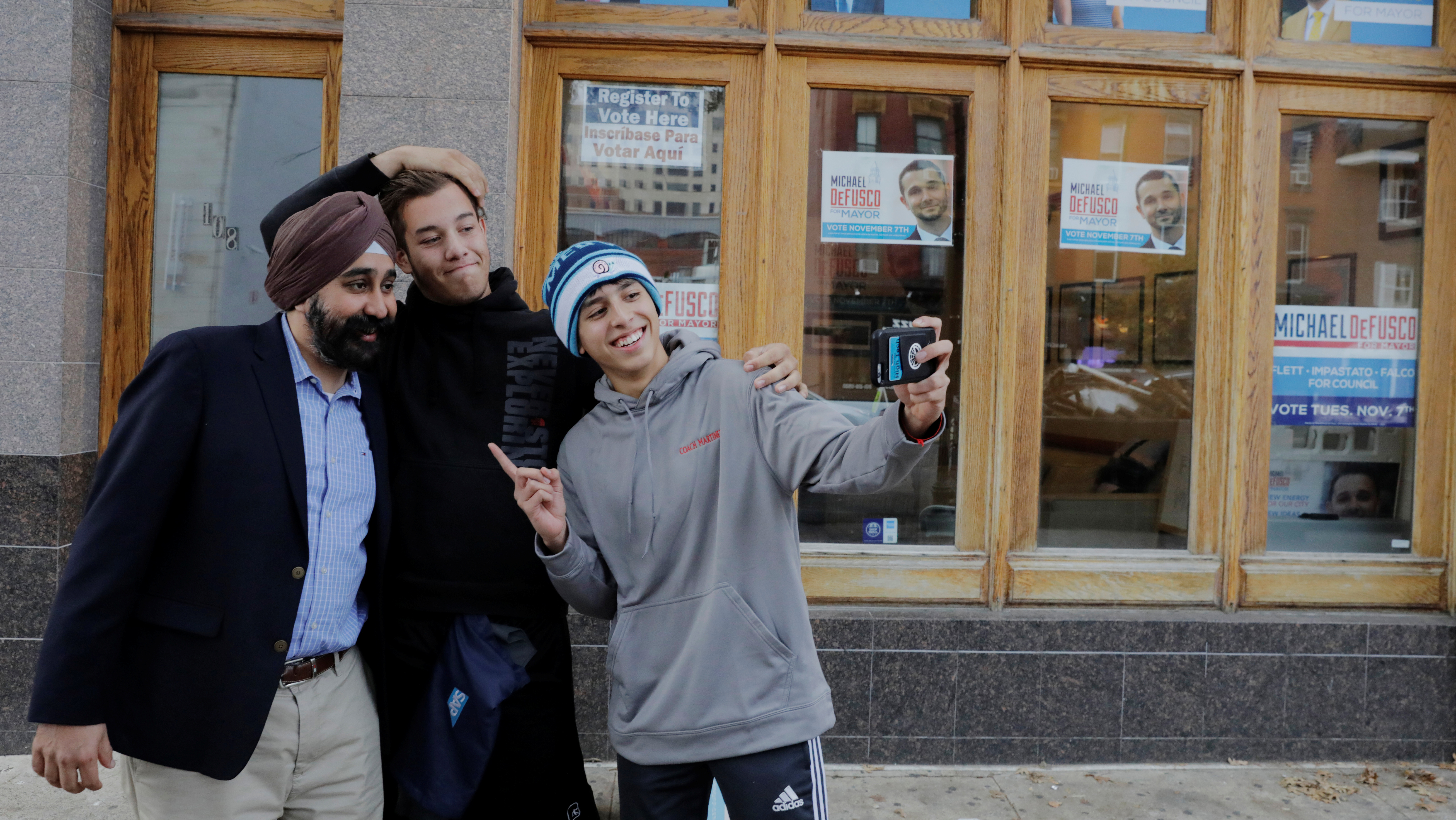 Hoboken, New Jersey Mayor-elect Ravi Bhalla greets supporters as he walks down the street in Hoboken, New Jersey, U.S., November 9, 2017. REUTERS/Lucas Jackson - RC1BFD91C9D0
