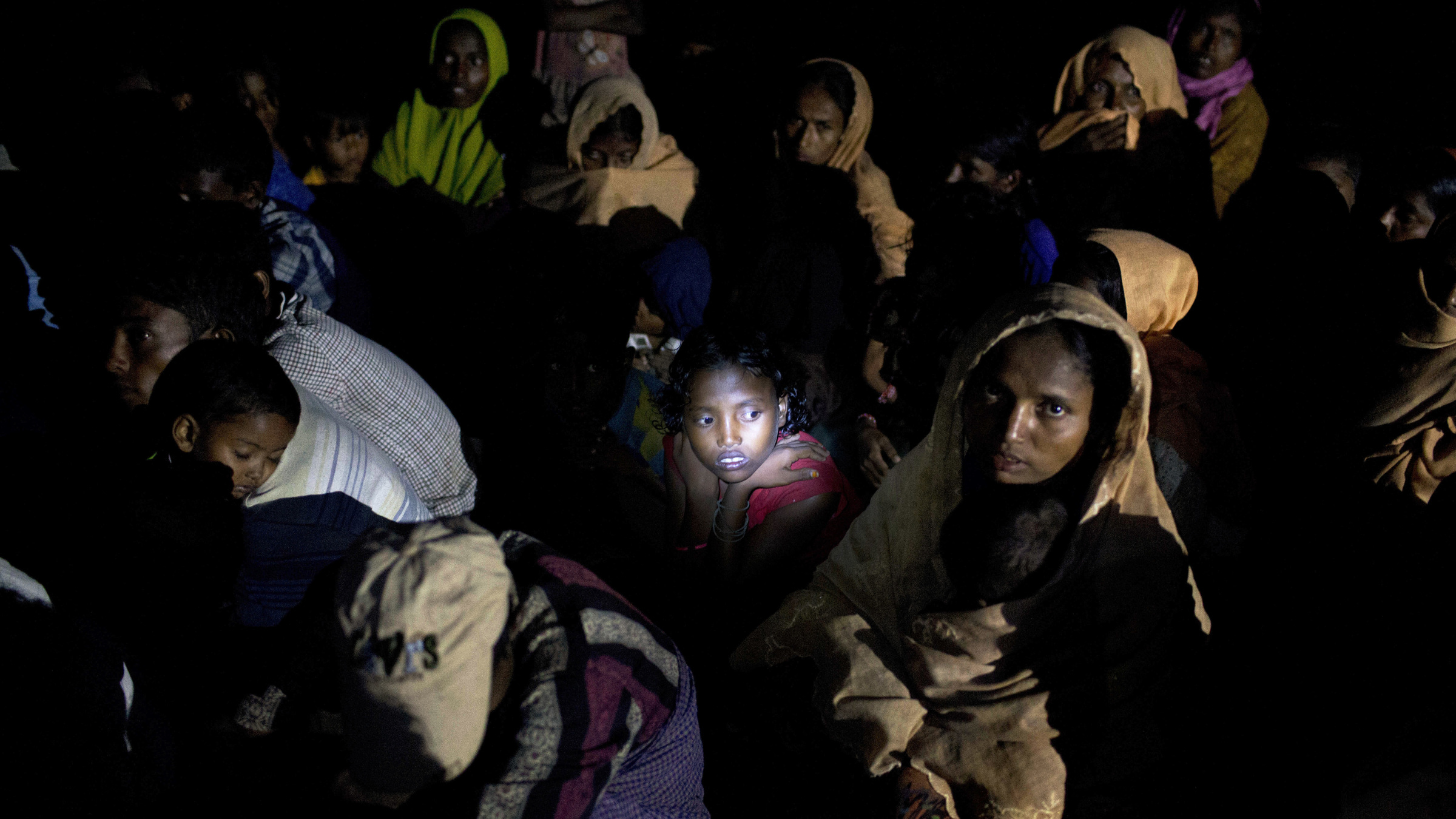 """Light from a torch falls on the face of a Rohingya Muslim girl sitting with a group on a raft made with plastic containers on which they crossed over from Myanmar into Bangladesh, as they wait for the permission to proceed forward, near Shah Porir Dwip, Bangladesh, Friday, Nov. 10, 2017. U.N. Secretary-General Antonio Guterres said Friday it is """"an absolutely essential priority"""" to stop all violence against Myanmar's Rohingya Muslims, allow them to return to their homes, and grant them legal status."""