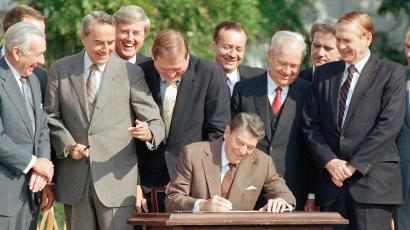 Lawmakers watch closely as Pres. Ronald Reagan signs into law a landmark tax overhaul on the White House South Lawn, Oct. 22, 1986, Washington, D.C. From left, are: Senate Majority Leader Robert Dole of Kansas, Rep. Raymond McGrath, R-N.Y.; Rep. Dan Rostenkowski, D-Ill., Rep. Frank Guerini, D-N.J.; Sen. Russell Long, D-La.; Rep. William Coyne, D-Pa., and Rep. John Duncan, R-Tenn.