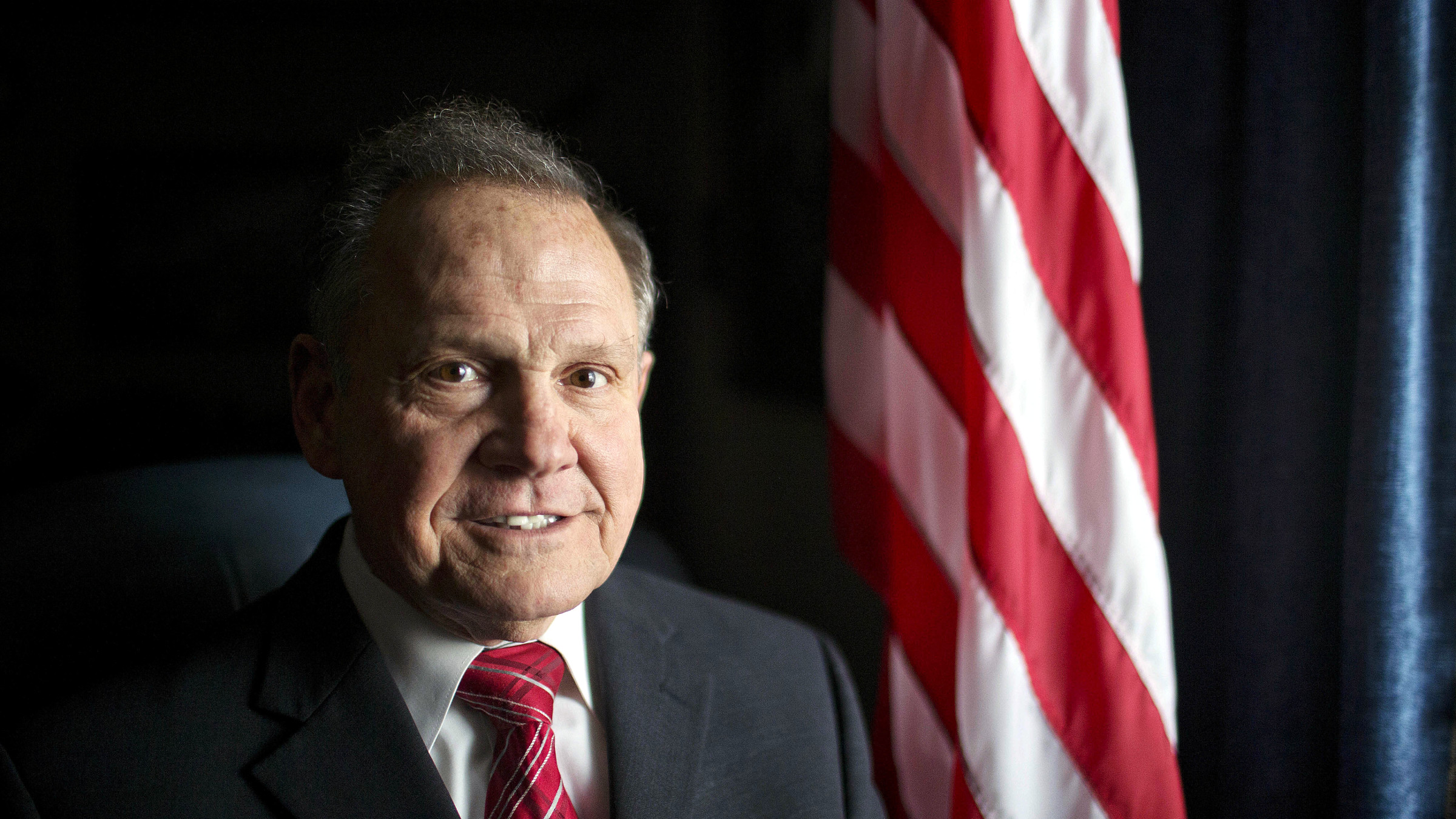 In this Feb. 17, 2015, file photo, Alabama Chief Justice Roy Moore poses in front the the American flag in Montgomery, Ala. The chief justice continues to fight against gay marriage in Alabama. Moore has been suspended from office after the Judicial Inquiry Commission accused him of violating the canons of judicial ethics with his actions during the fight over sane-sex marriage