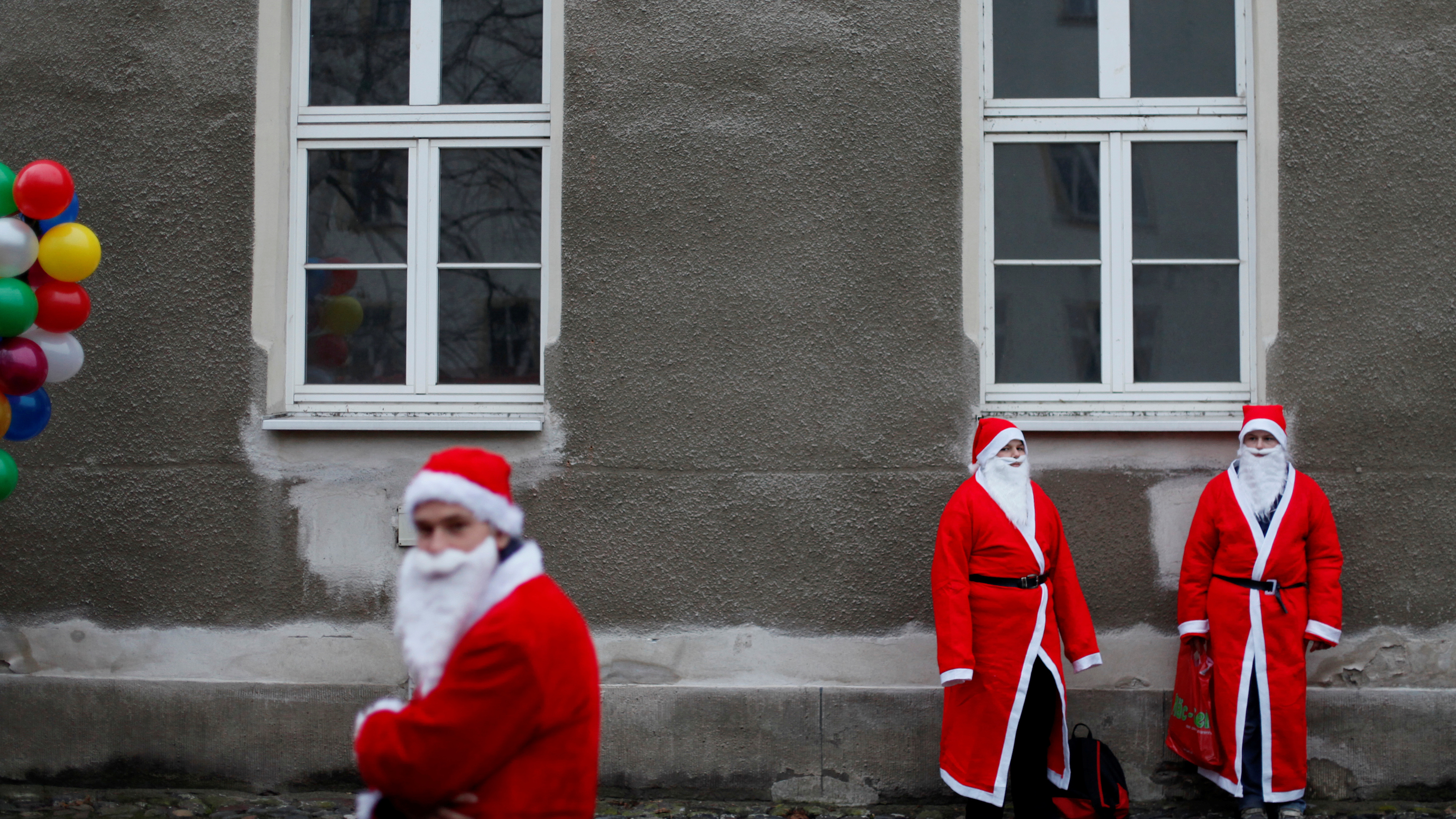 Young men dressed in Santa Claus costumes attend the annual Santa Claus parade in Brandenburg, southwest of Berlin December 6, 2008. Some 106 decorated vehicles and more than 2,000 people participated in the parade on Saturday. REUTERS/Johannes Eisele (GERMANY) - BM2E4C61GC101