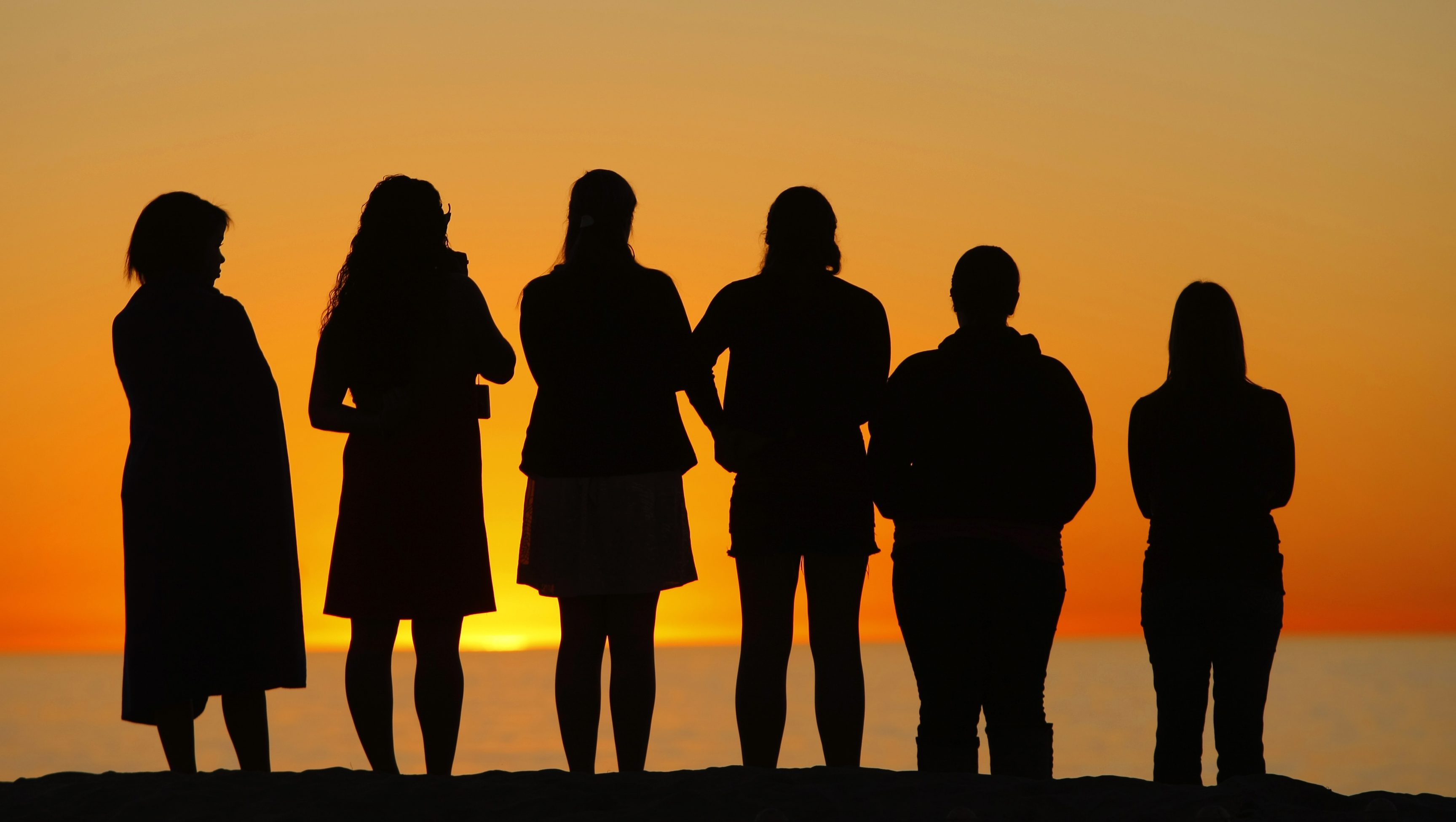 Girls gather to watch the sun set at Moonlight beach in Encinitas, California January 13, 2009.  REUTERS/Mike Blake  (UNITED STATES) - GM1E51E0W9Z01