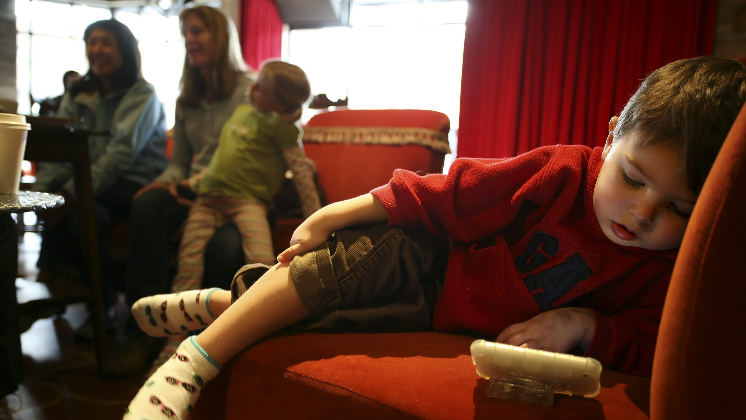 Matthew West, 3, watches a video on his Mom's iPhone while she talks with friends at Starbucks' Roy Street Coffee and Tea in Seattle, Washington, March 25, 2010.