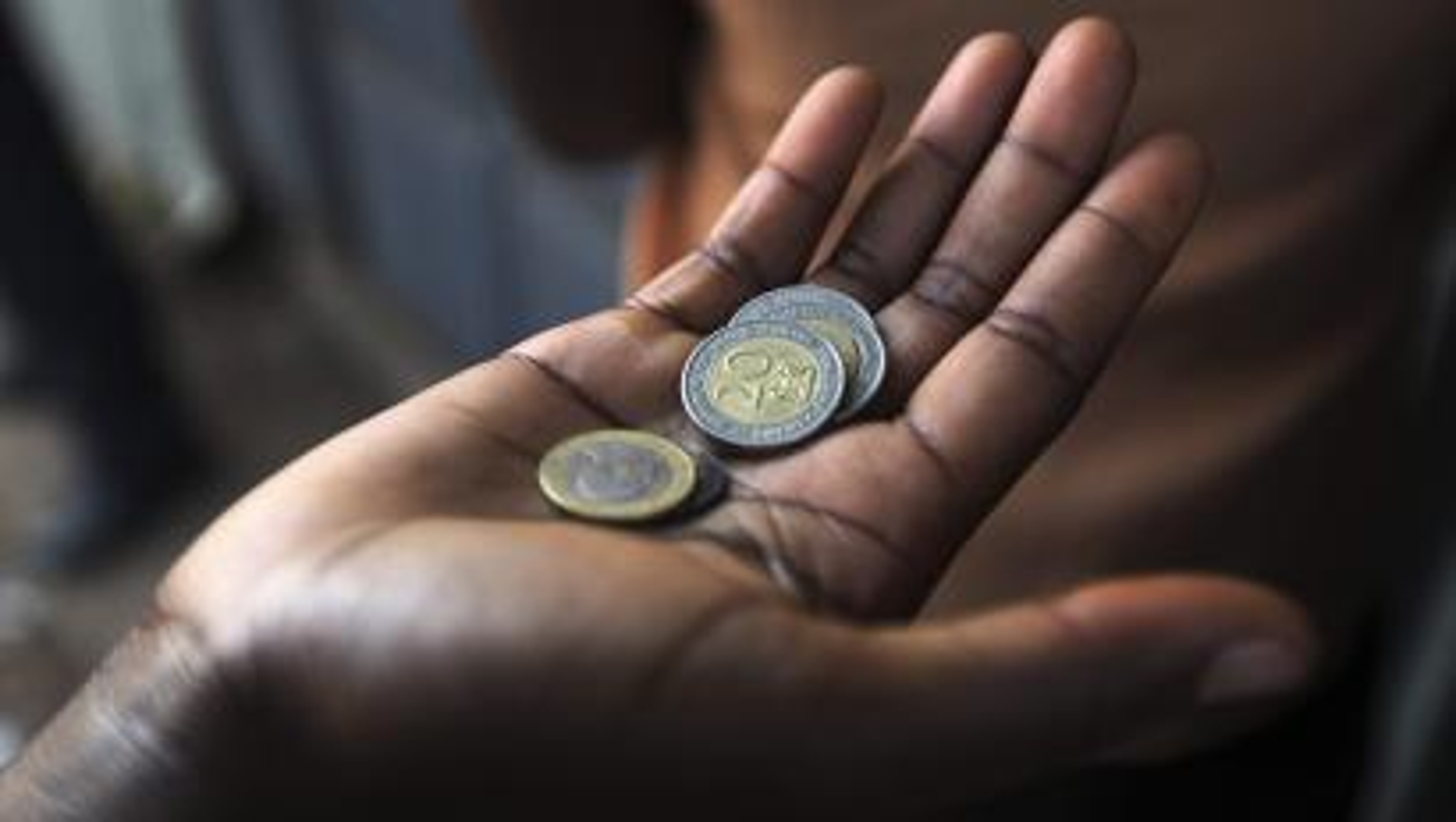A customer has his money ready at a store in the sprawling Kibera slums in Kenya's capital Nairobi April 23, 2010.