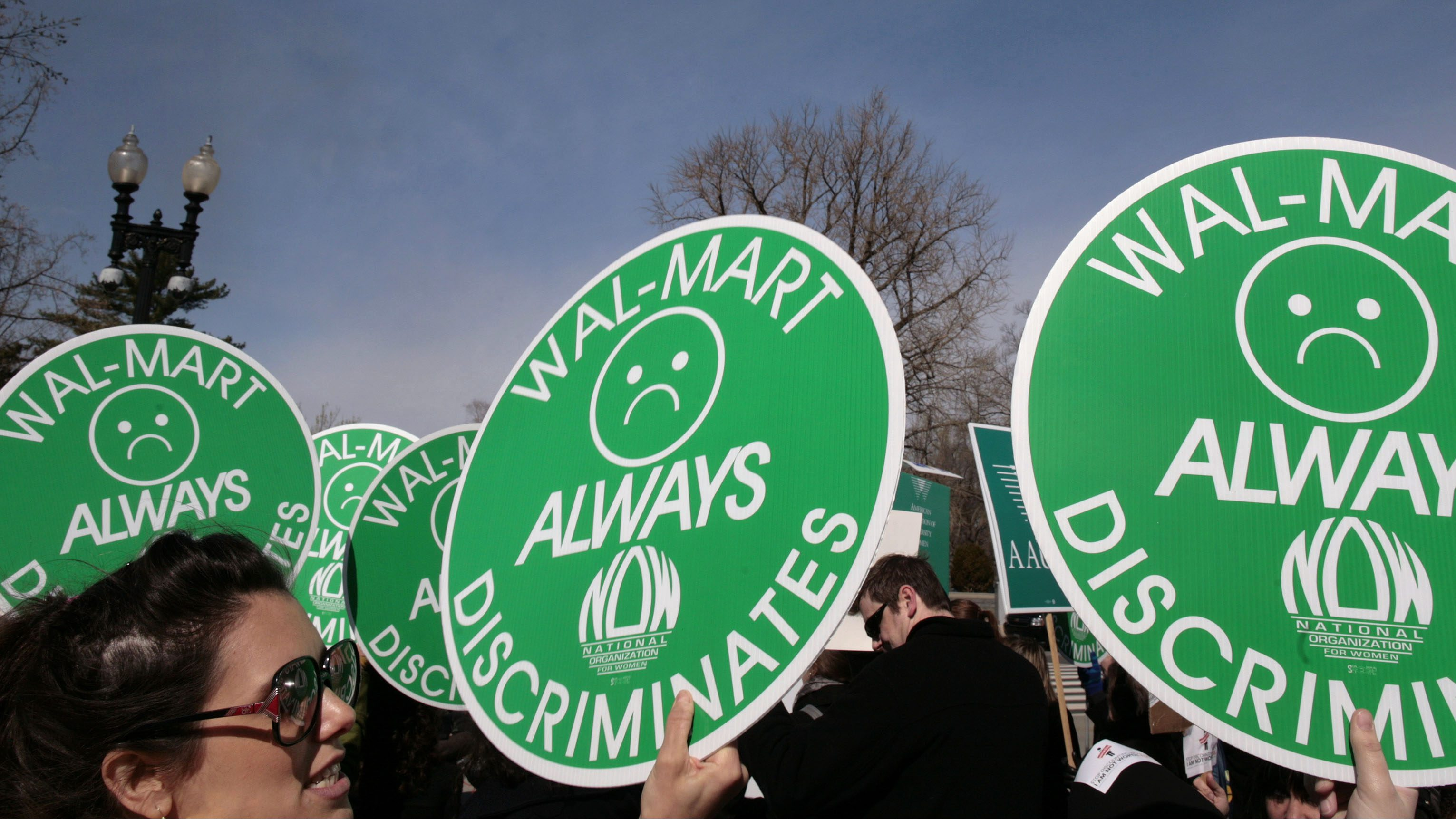 Women hold anti-walmart signs at supreme court case in 2011