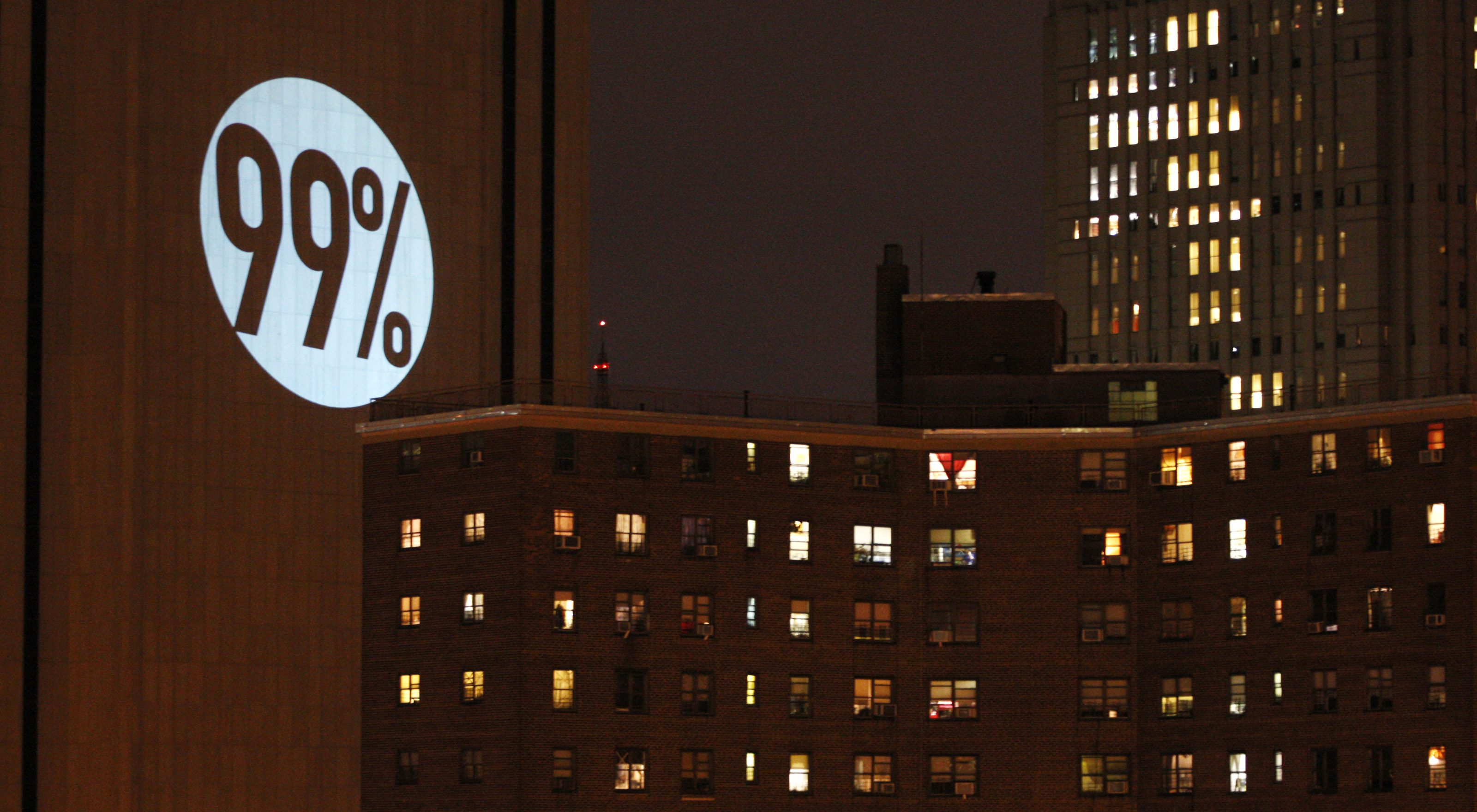 A 99% sign is projected on the Verizon Building by Occupy Wall Street demonstrators during what protest organizers called a day of action in New York November 17, 2011. New York police prevented protesters from shutting down Wall Street on Thursday, arresting more than 200 people in repeated clashes with an unexpectedly small but spirited Occupy Wall Street rally.     (UNITED STATES - Tags: BUSINESS CIVIL UNREST CITYSPACE TPX IMAGES OF THE DAY) - GM1E7BI0YTF01