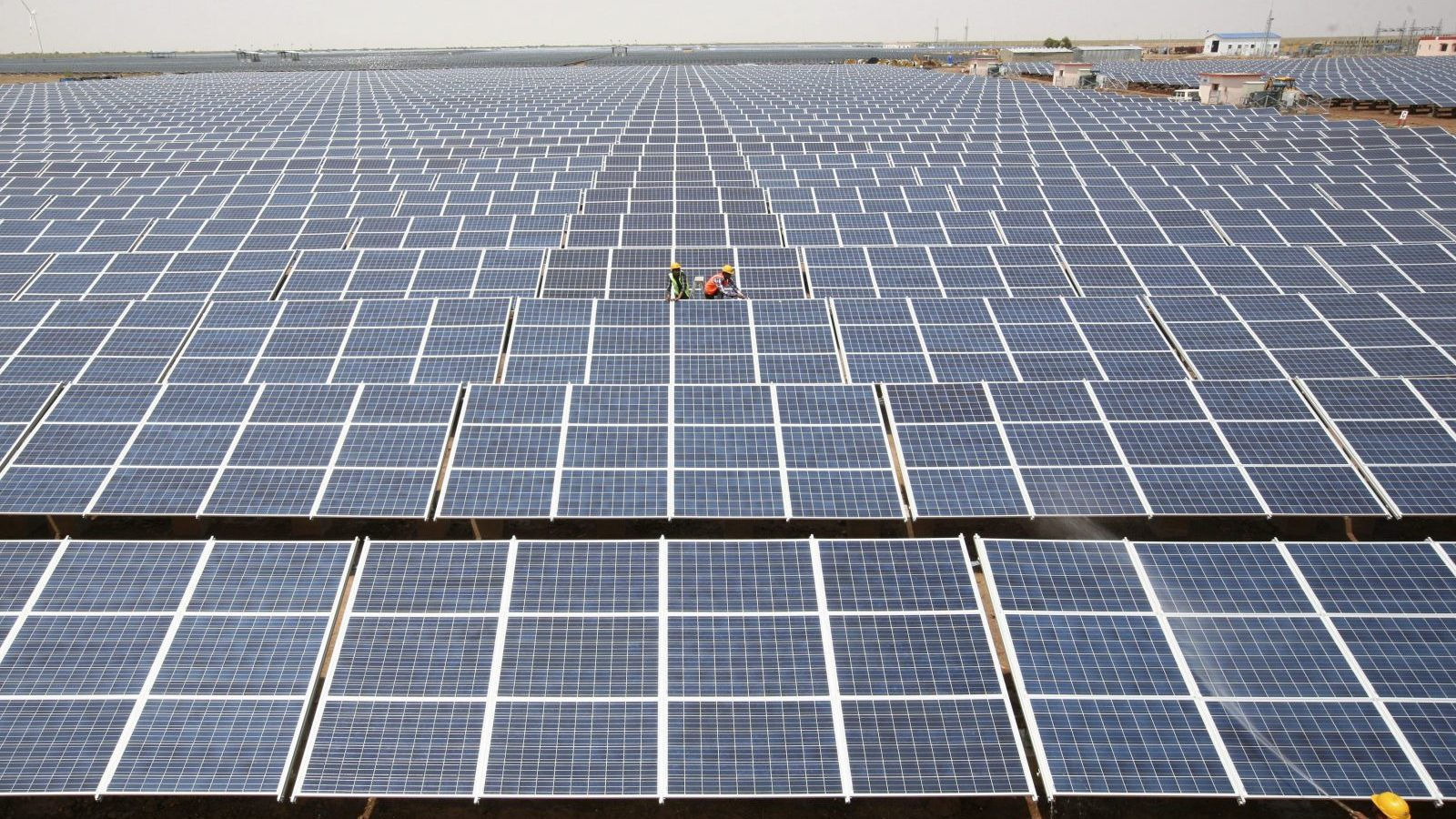 Workers install photovoltaic solar panels at the Gujarat solar park under construction in Charanka village in Patan district of the western Indian state of Gujarat April 14, 2012. According to officials, the solar park is the largest in India which will generate 210 megawatts and will be operational from April 19, 2012. REUTERS/Amit Dave (INDIA - Tags: BUSINESS ENERGY) - GM1E84E1OWQ01