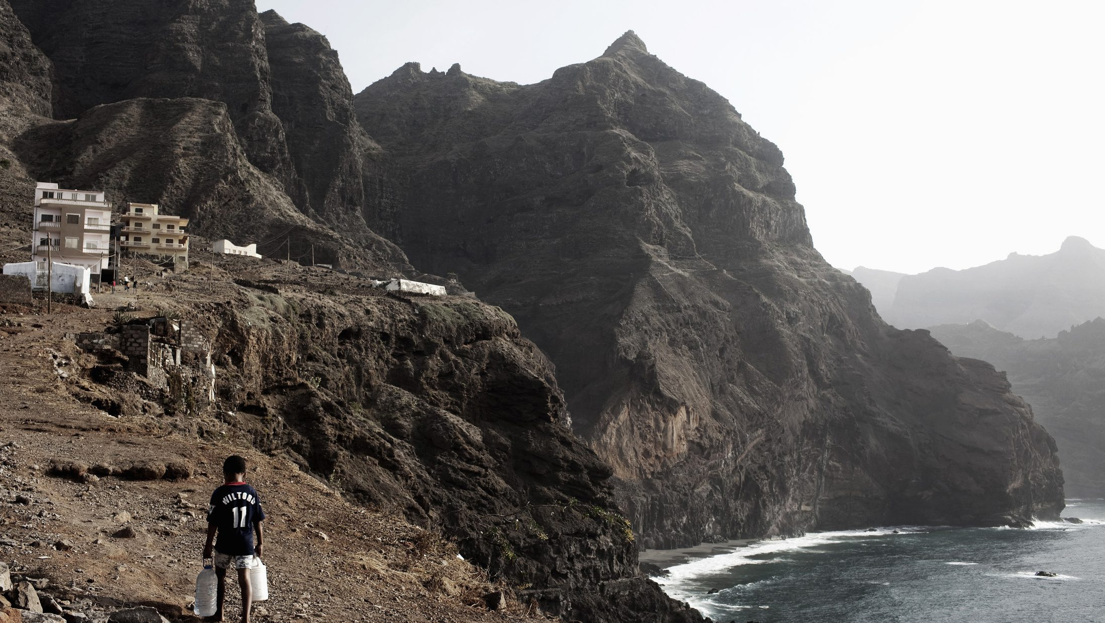 A boy carries containers of water uphill in the town of Porta do Sol on the island of Santo Antao in Cape Verde