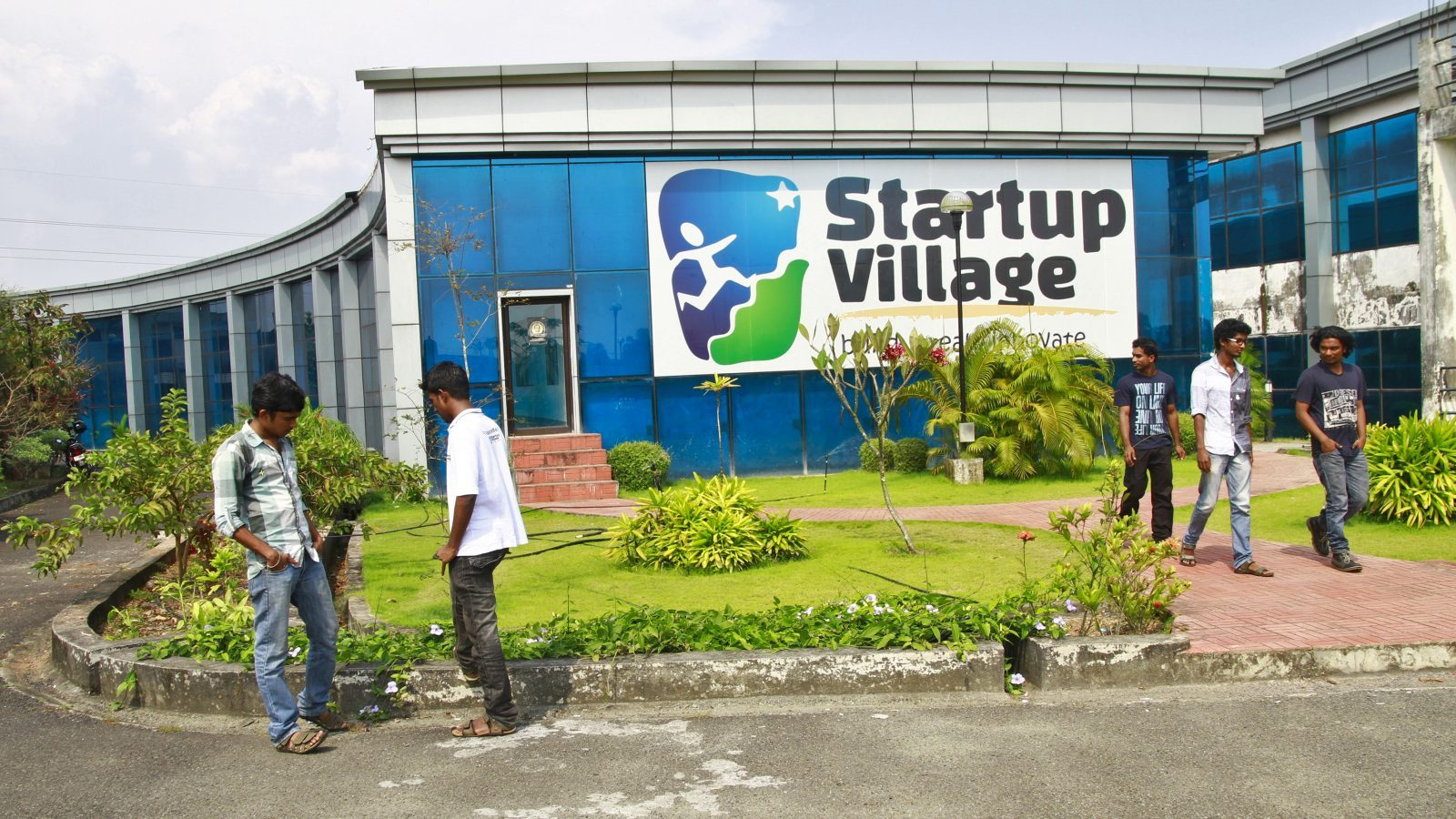 Employees stand outside the Start-up Village in Kinfra High Tech Park in the southern Indian city of Kochi October 13, 2012. Three decades after Infosys, India's second-largest software service provider, was founded by middle-class engineers, the country has failed to create an enabling environment for first-generation entrepreneurs. Startup Village wants to break the logjam by helping engineers develop 1,000 Internet and mobile companies in the next 10 years. It provides its members with office space, guidance and a chance to hobnob with the stars of the tech industry. But critics say this may not even be the beginning of a game-changer unless India deals with a host of other impediments - from red tape to a lack of innovation and a dearth of investors - that are blocking entrepreneurship in Asia's third-largest economy. To match Feature INDIA-TECHVILLAGE/ Picture taken October 13, 2012. REUTERS/Sivaram V (INDIA - Tags: BUSINESS SCIENCE TECHNOLOGY EMPLOYMENT) - GM1E8C403NM01