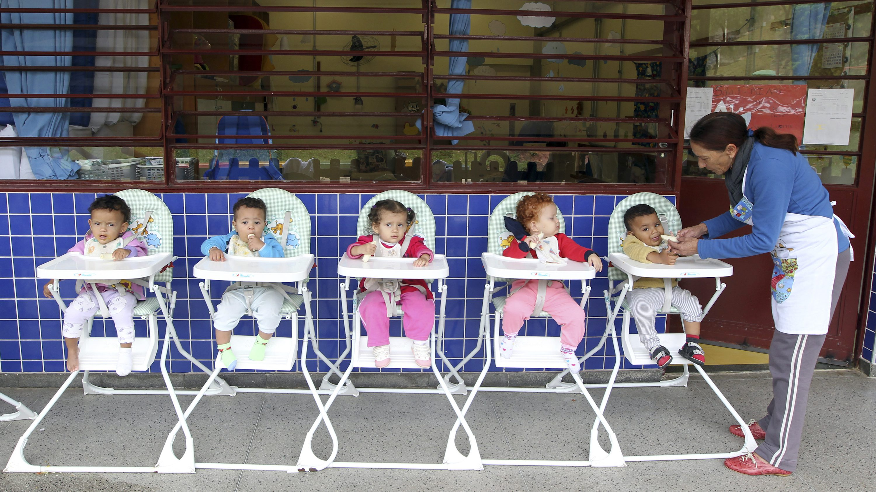 Children sit in high chairs as a woman feeds them lunch at a public school in Sao Paulo March 21, 2013.