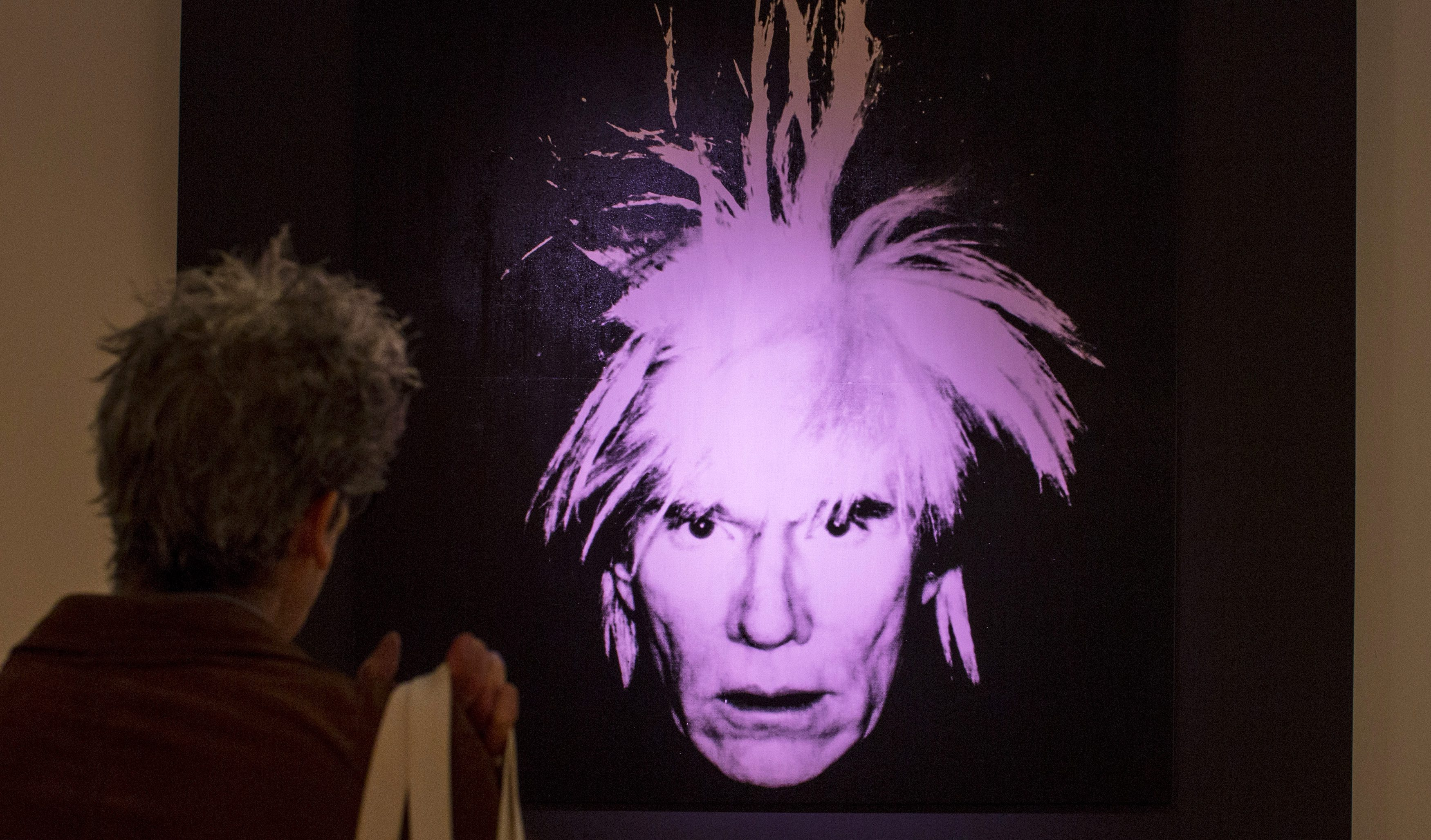 """A man examines """"Self-Portrait"""" by Andy Warhol during a media preview at Christie's auction house in New York, October 31, 2014. Christie's estimates its postwar and contemporary art auction will total more than $600 million, the highest pre-sale estimate ever for any single sale. REUTERS/Brendan McDermid (UNITED STATES - Tags: ENTERTAINMENT SOCIETY) - GM1EAB10BG701"""