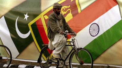 MAN RIDES PAST SAARC BANNER IN ISLAMABAD.