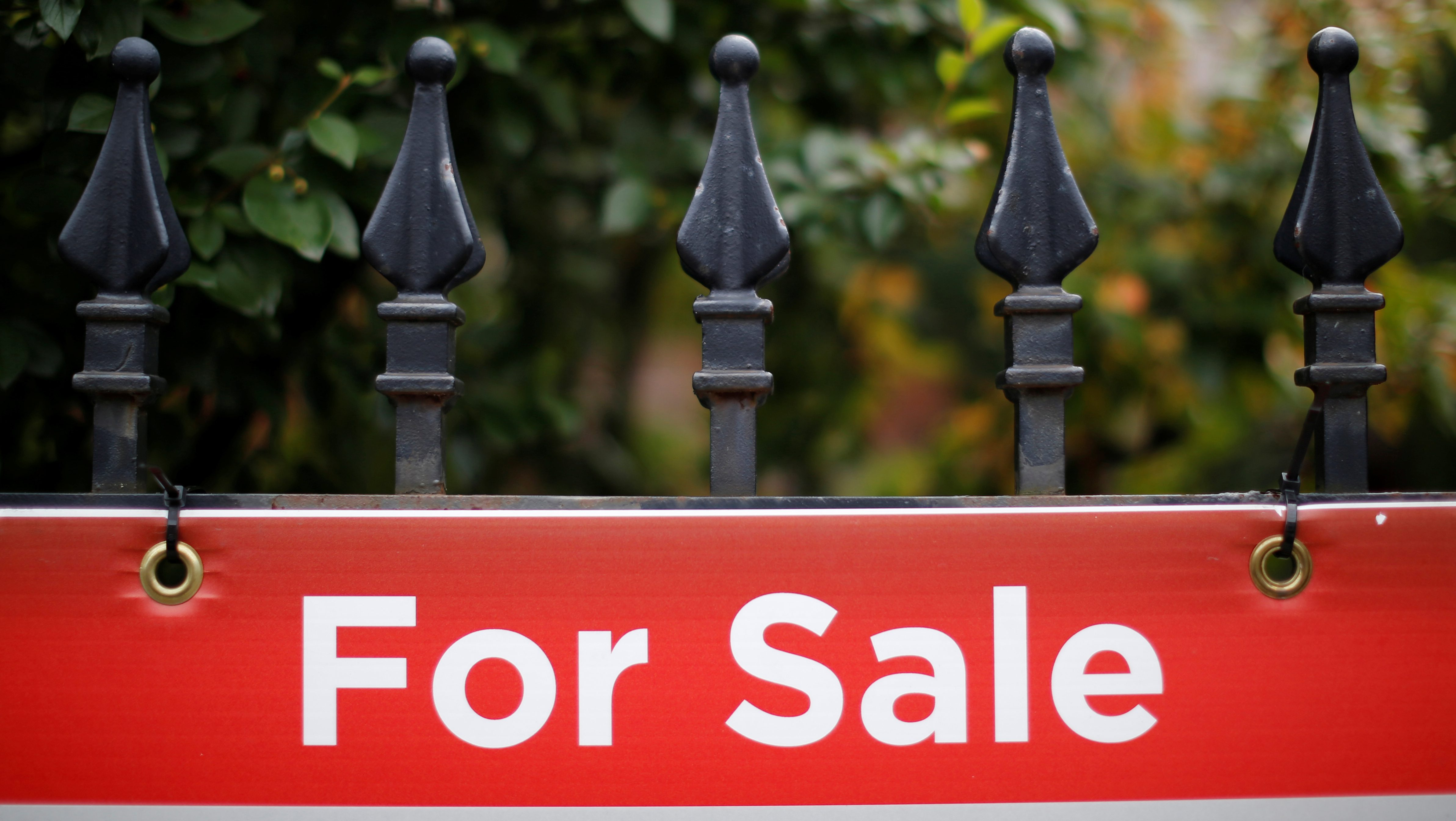 A real estate sign is seen hanging on a fence in front of a house for sale in Ottawa, Ontario, Canada.