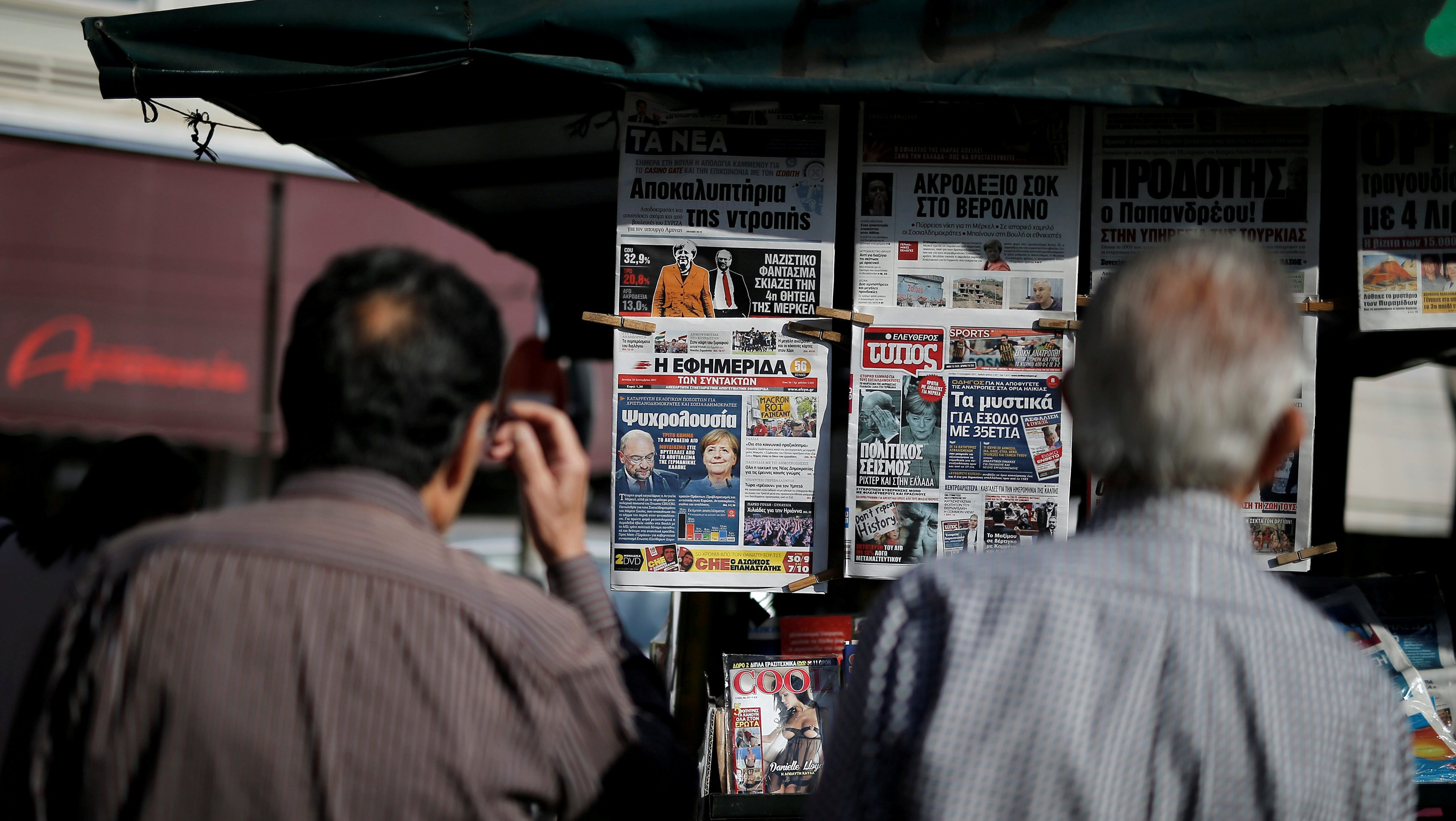 People read newspaper headlines on the German elections results at a kiosk in Athens, Greece September 25, 2017. REUTERS/Alkis Konstantinidis - RC14DC3D3E80