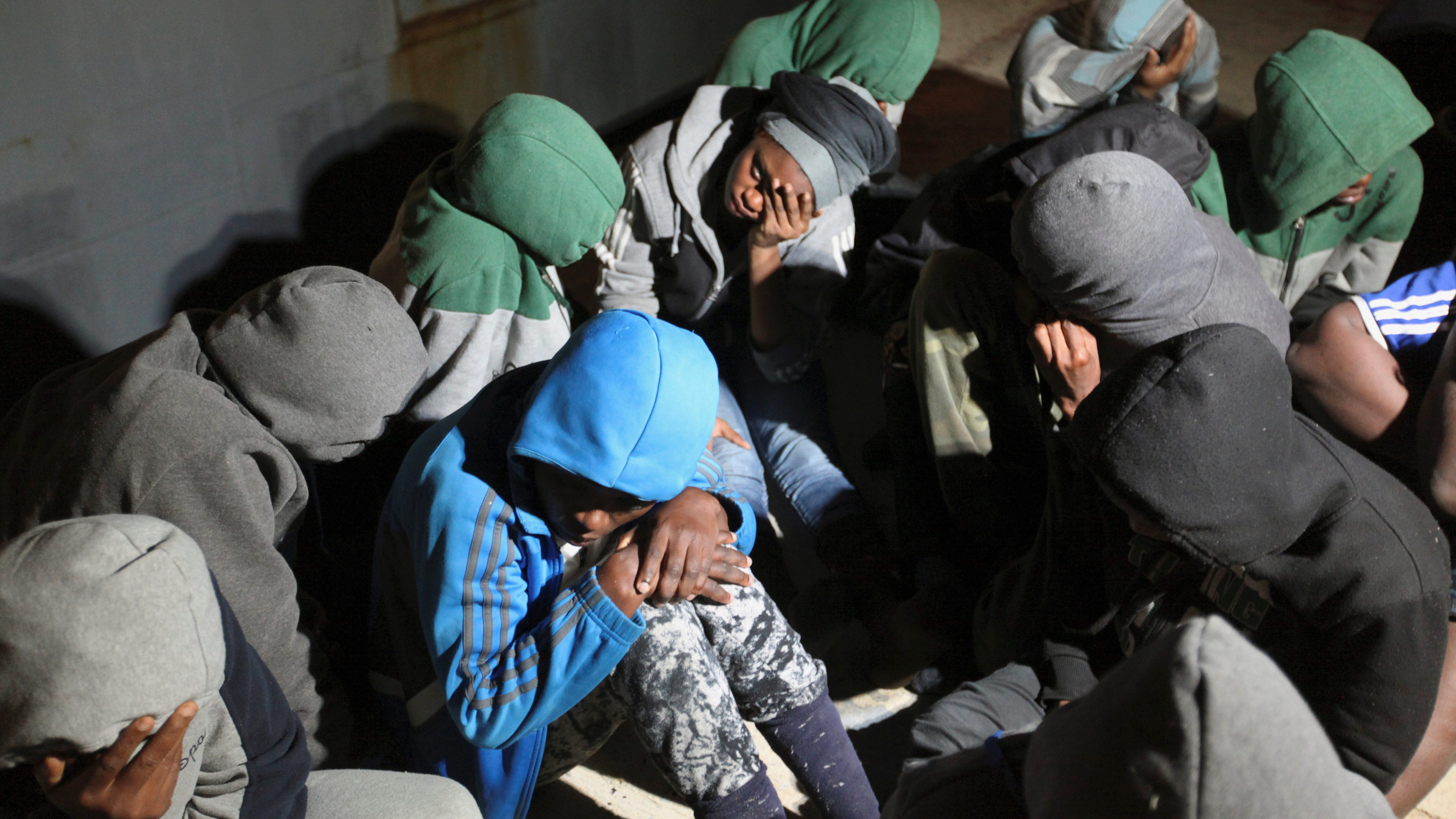 Migrants sit at a naval base after they were rescued by Libyan coastguard, in Tripoli
