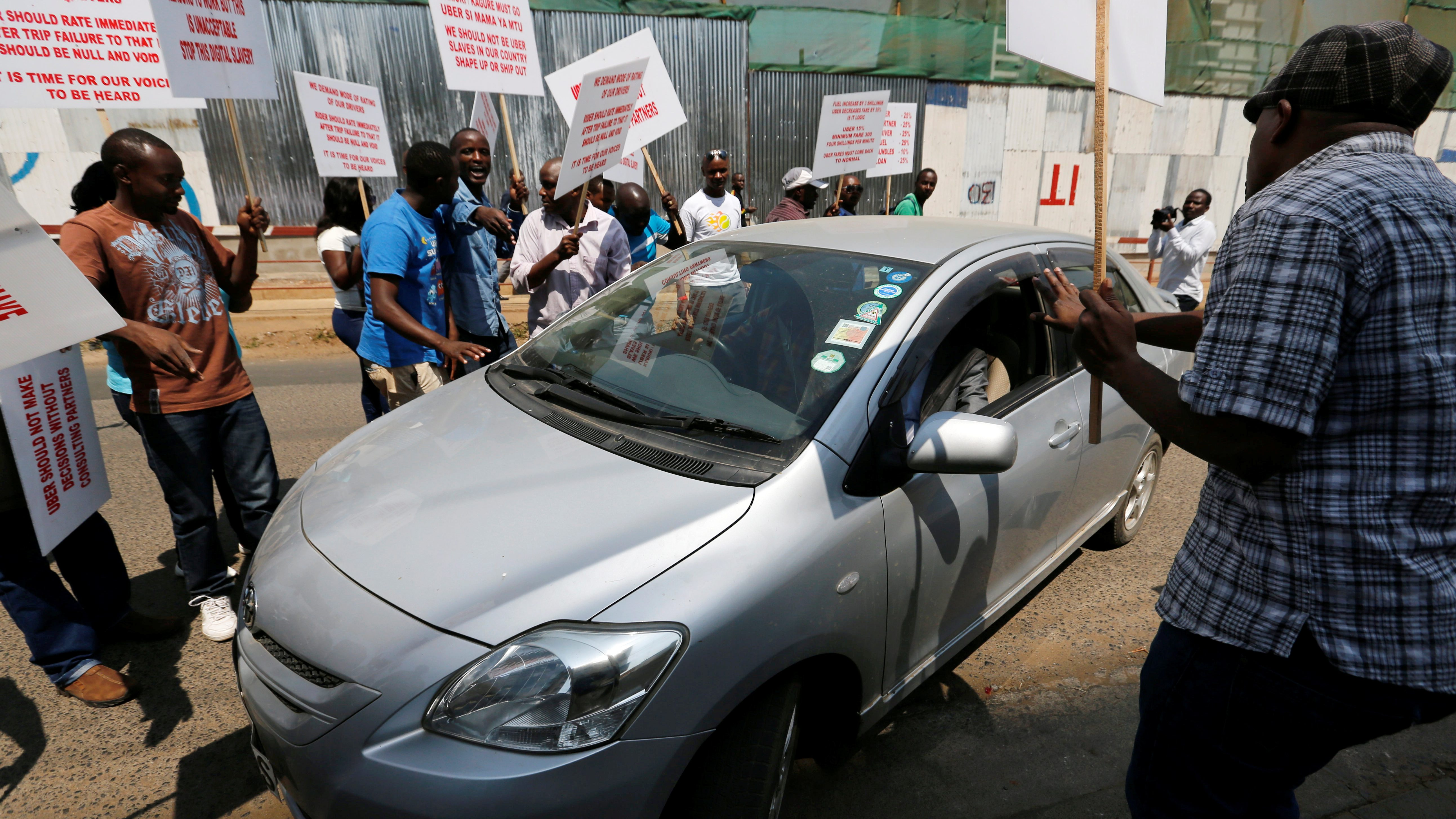 Kenyan taxi drivers signed up to ride-hailing service Uber attempt to eject a passenger from one of the Uber operating taxis during a strike in Kenya's capital Nairobi