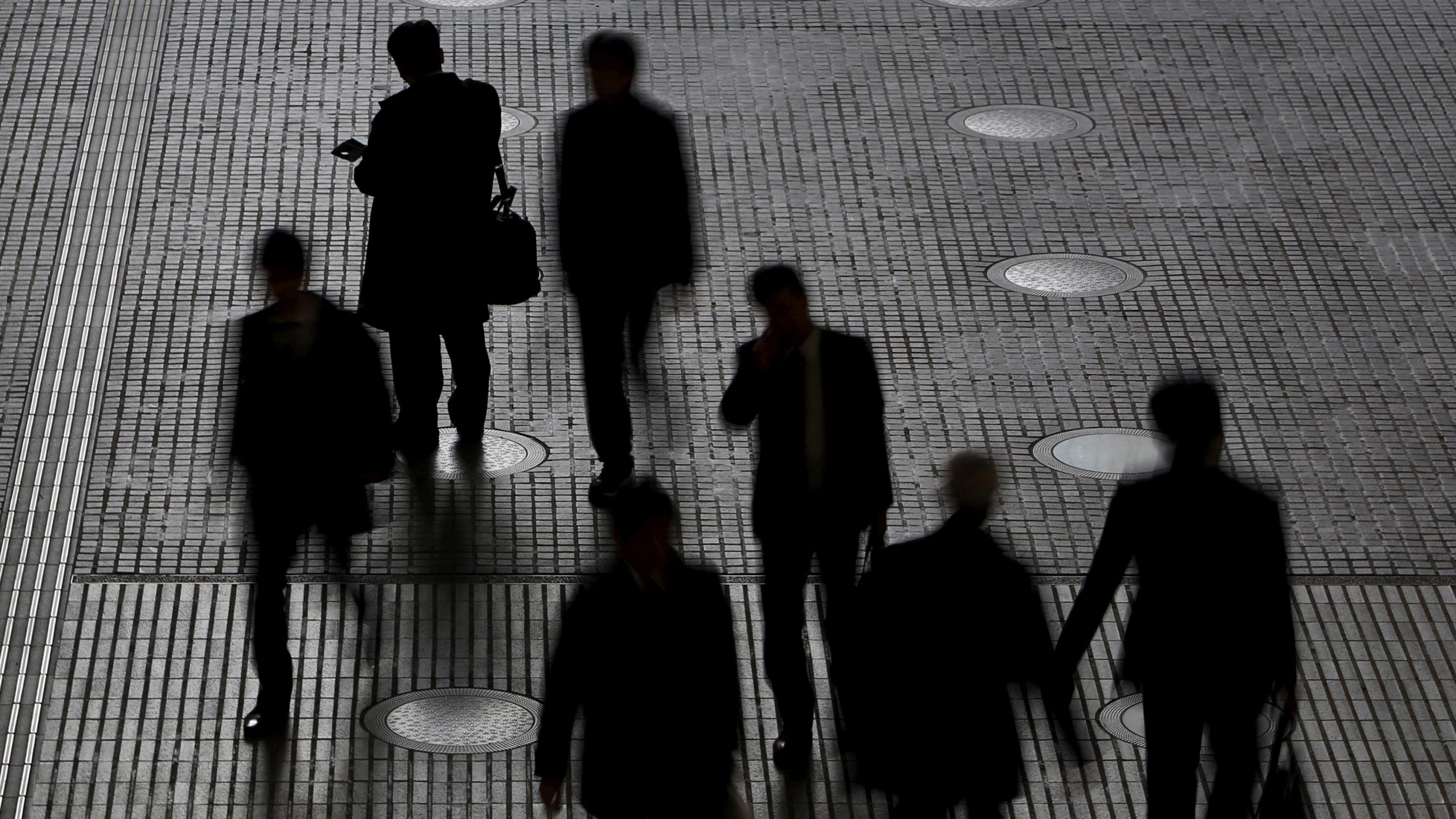 People walk at an office building at a business district in Tokyo, Japan, February 29, 2016.