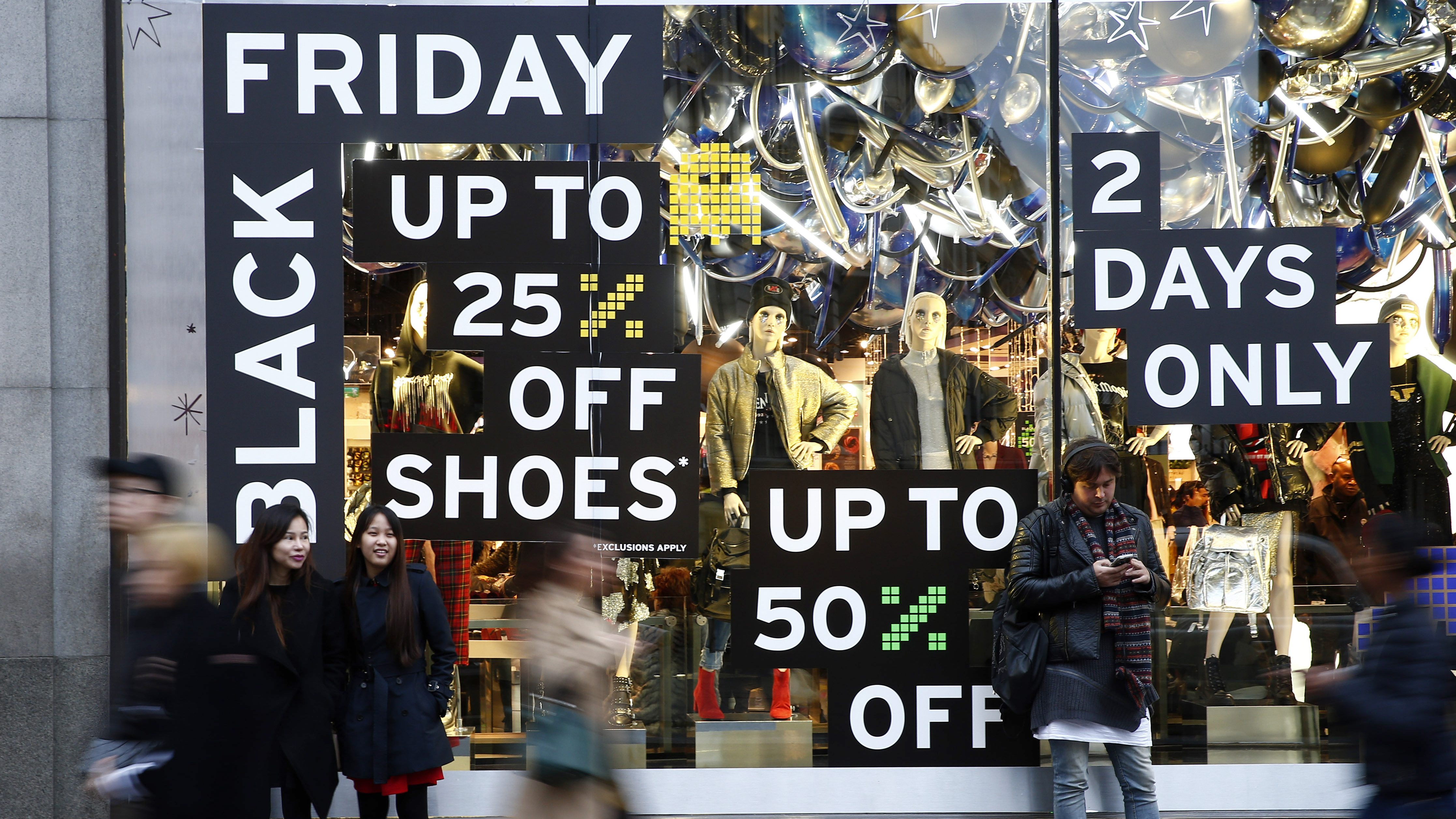 """Shoppers walk past a store promoting """"Black Friday"""" in London."""