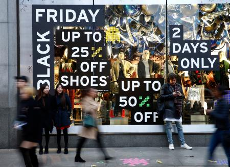 "Shoppers walk past a store promoting ""Black Friday"" in London, Britain November 27, 2016. REUTERS/Peter Nicholls - LR1ECBR1B5AK2"