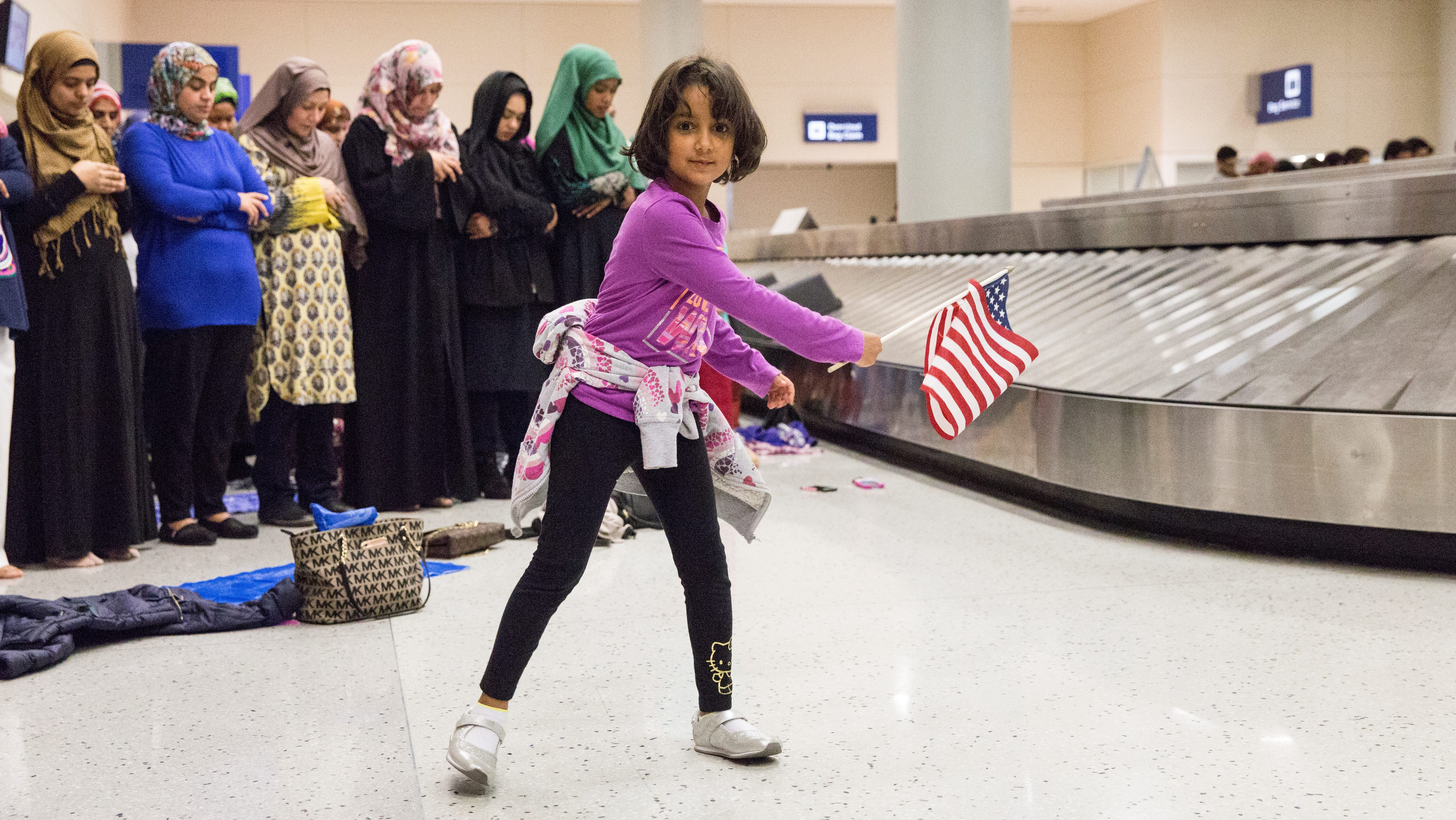 A young girl dances with an American flag in baggage claim while women pray behind her during a protest against the travel ban imposed by U.S. President Donald Trump's executive order, at Dallas/Fort Worth International Airport in Dallas, Texas, U.S. January 29, 2017.  REUTERS/Laura Buckman - RC11D43576E0