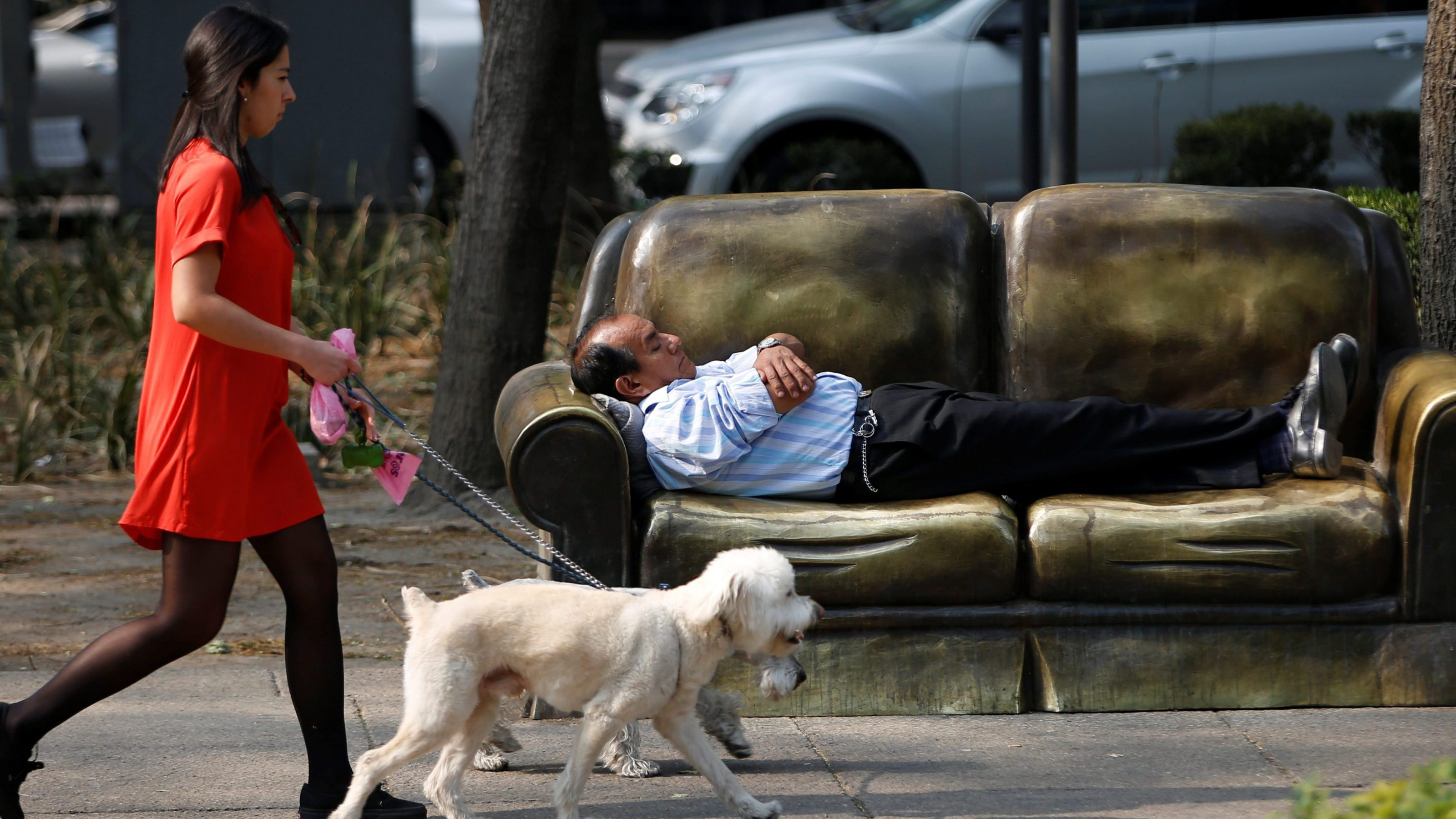 A man rests on a park bench in the shape of a sofa as a woman walks past with two dogs
