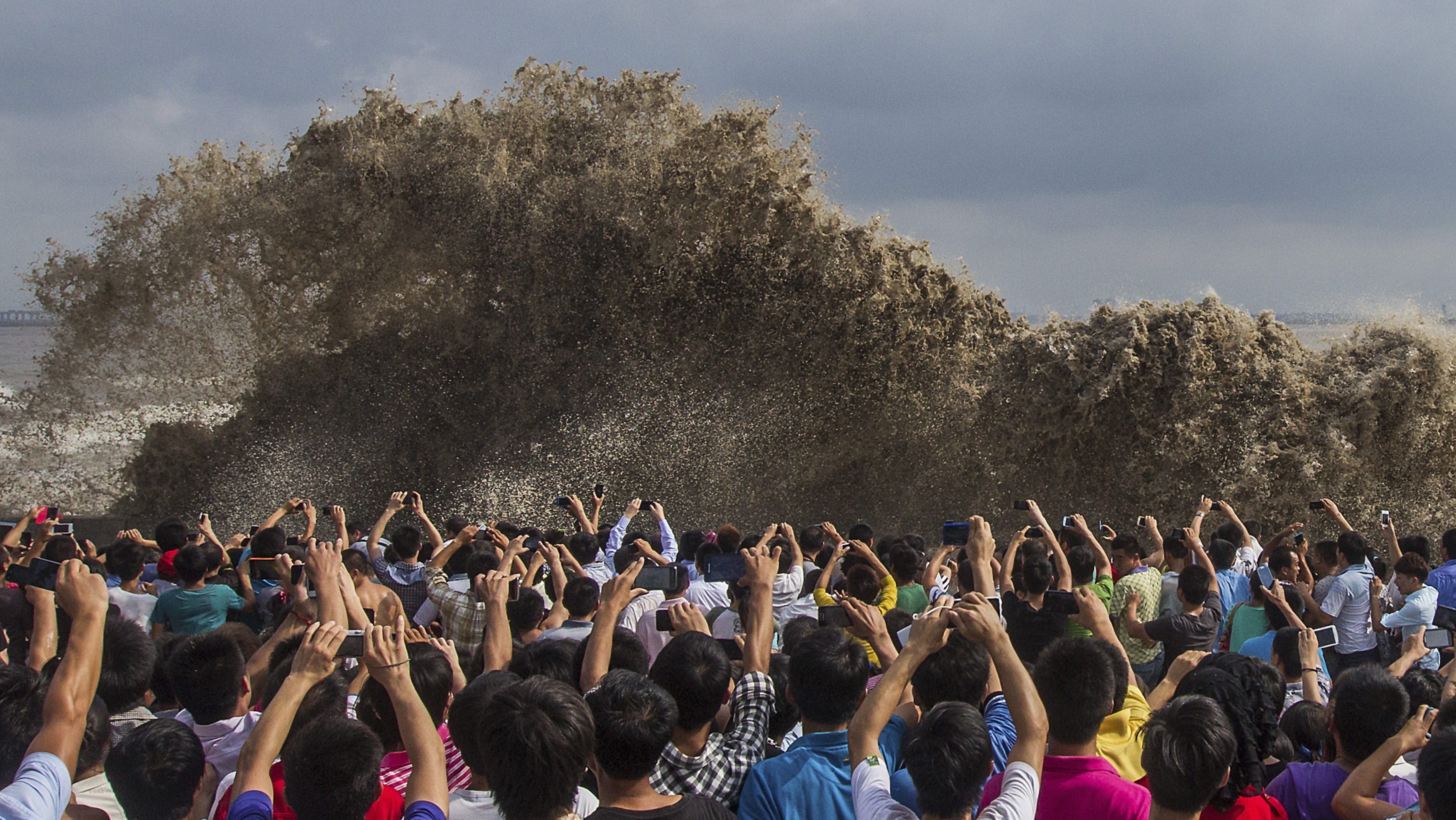 Visitors take pictures of tidal waves in Hangzhou, Zhejiang province, September 22, 2013.