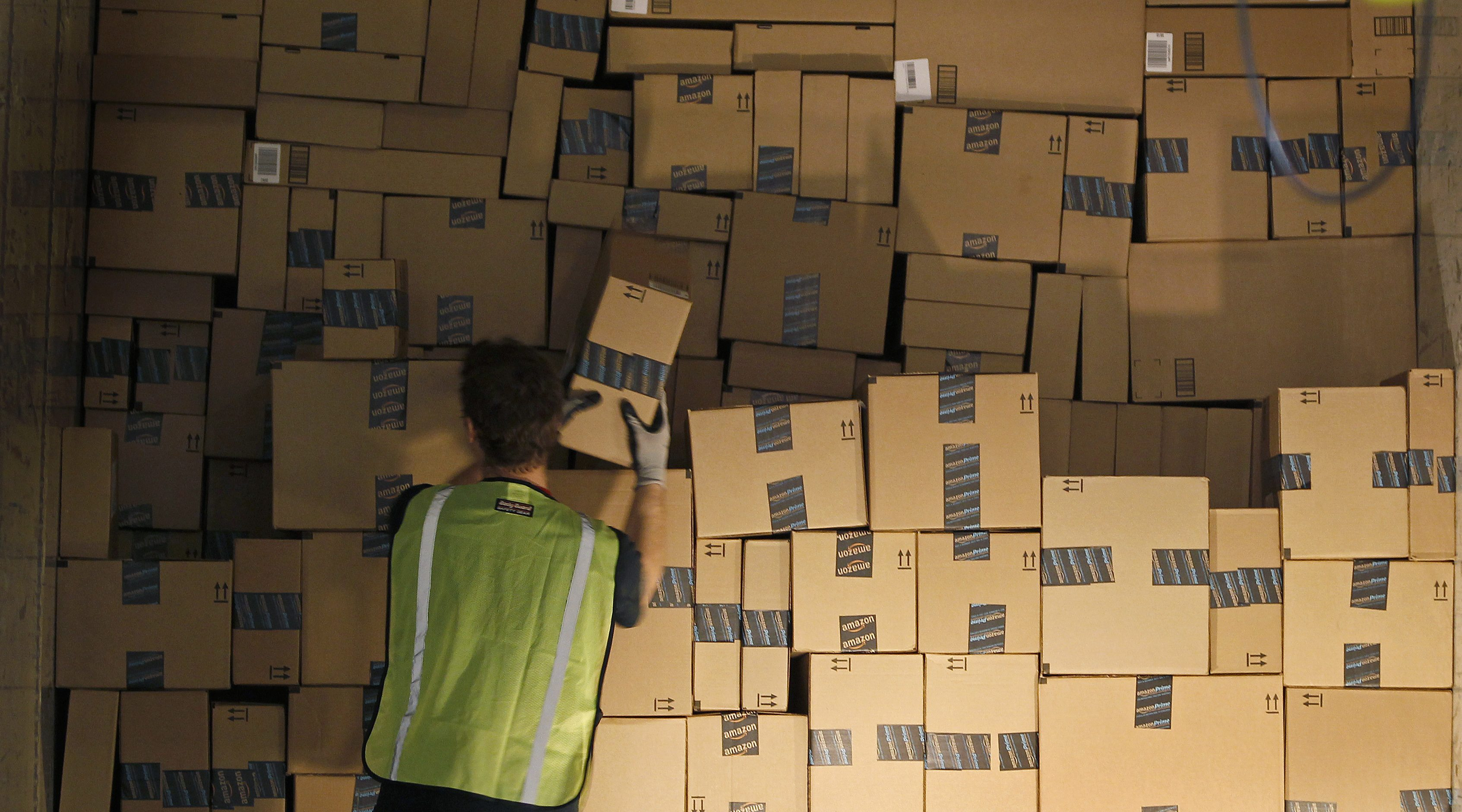 Worker stacks a shipping trailer with boxed items for delivery at Amazon's distribution center in Phoenix
