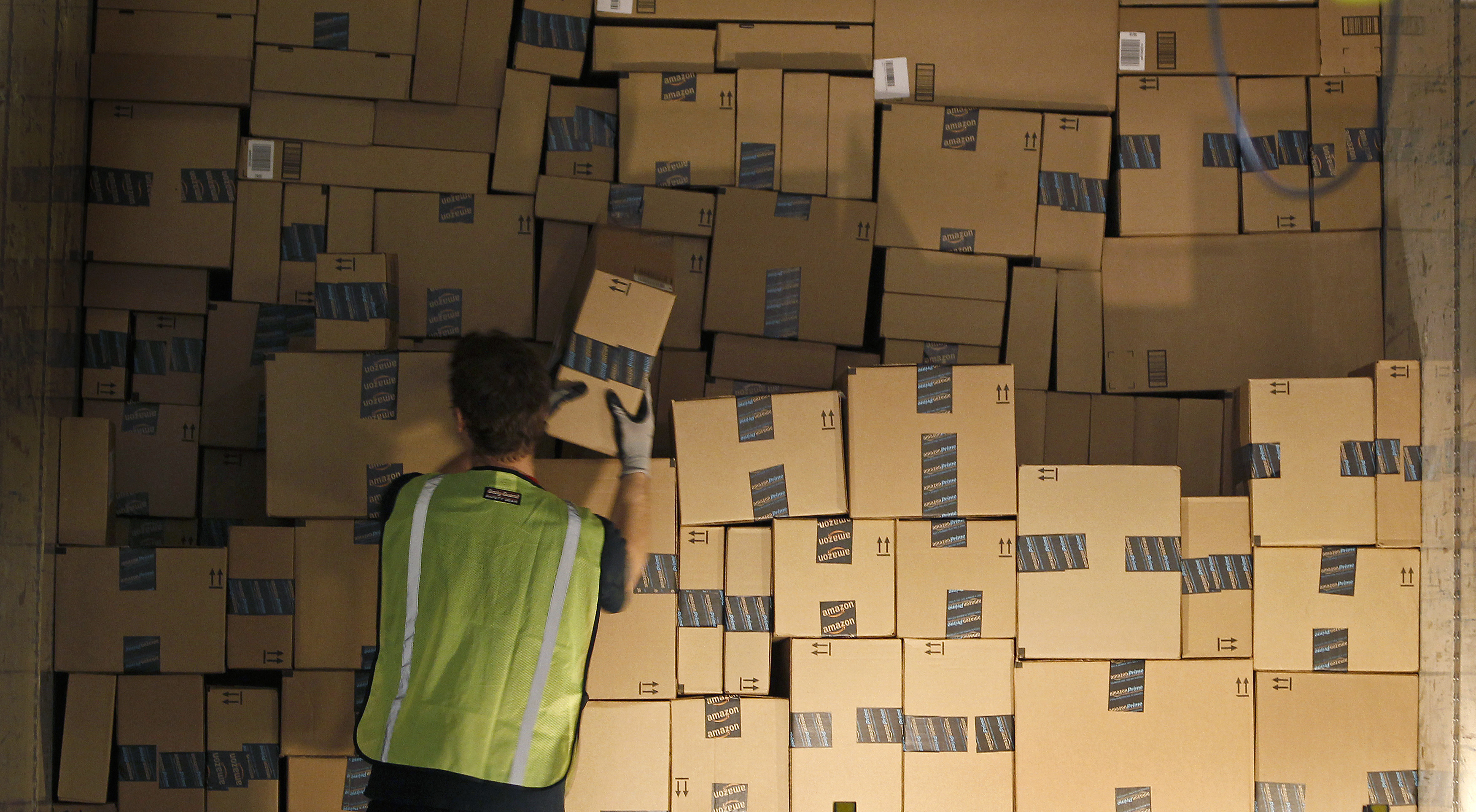 A worker stacks a shipping trailer with boxed items for delivery at Amazon's distribution center in Phoenix, Arizona November 22, 2013. The web-based retailer is preparing for Cyber Monday, traditionally the busiest day of the year for online purchases, which falls on December 2 in 2013.