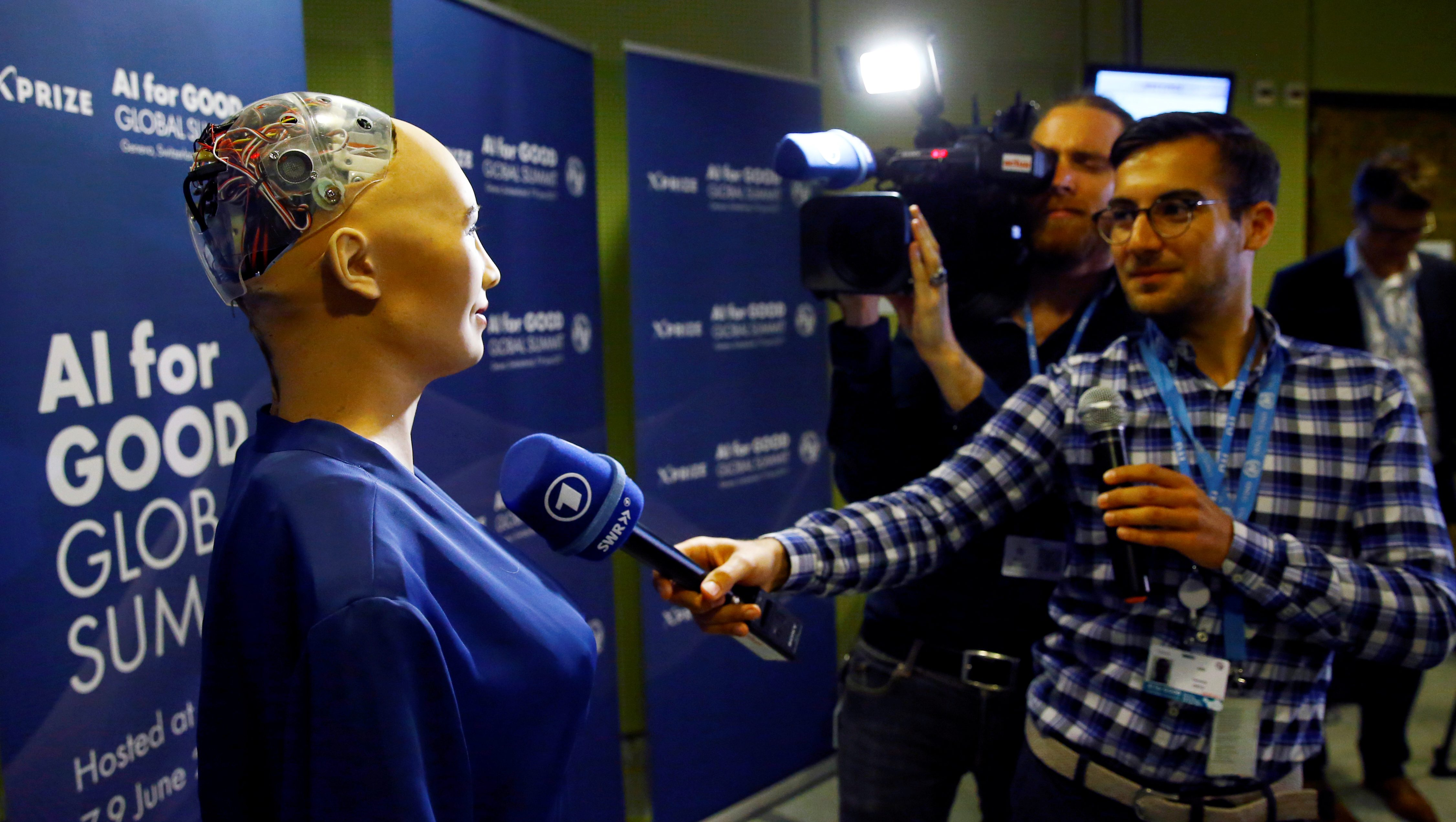 """A TV crew interviews Sophia, a robot integrating the latest technologies and artificial intelligence created by Hanson Robotics, during a presentation at the """"AI for Good"""" Global Summit at the International Telecommunication Union (ITU) in Geneva, Switzerland June 7, 2017. REUTERS/Denis Balibouse - RC167AA4E9D0"""