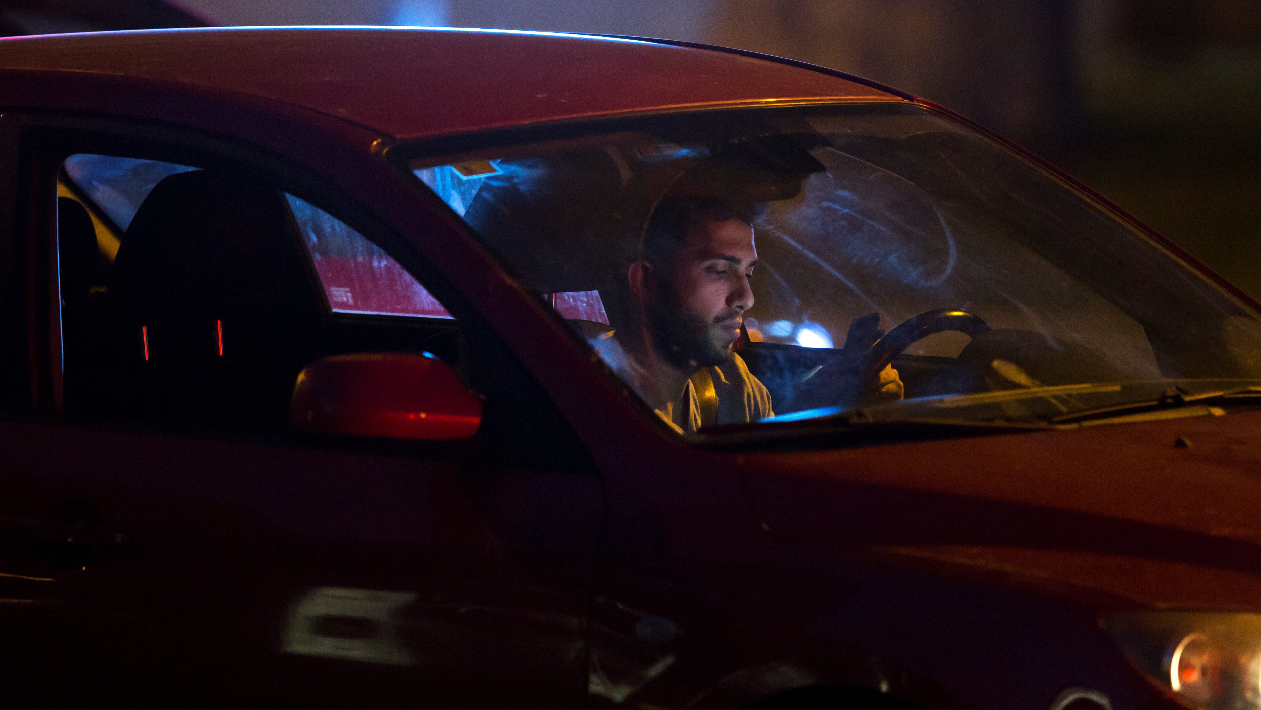 A man looks at his cell phone in a car in Madrid, Spain.