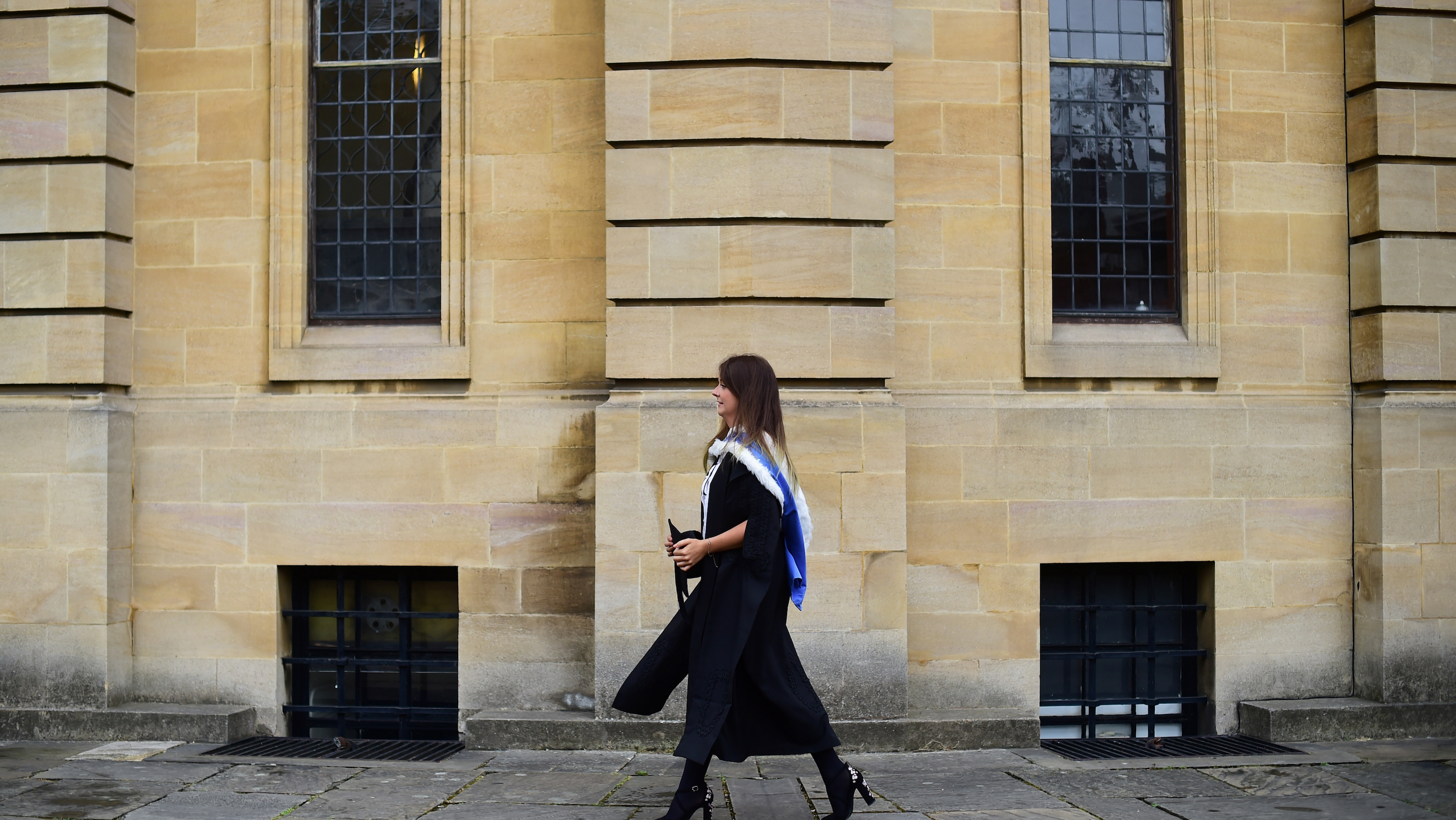 A graduate walks away after a graduation ceremony at Oxford University, in Oxford, Britain July 15, 2017. REUTERS/Hannah McKay - RC1E5D14AC00