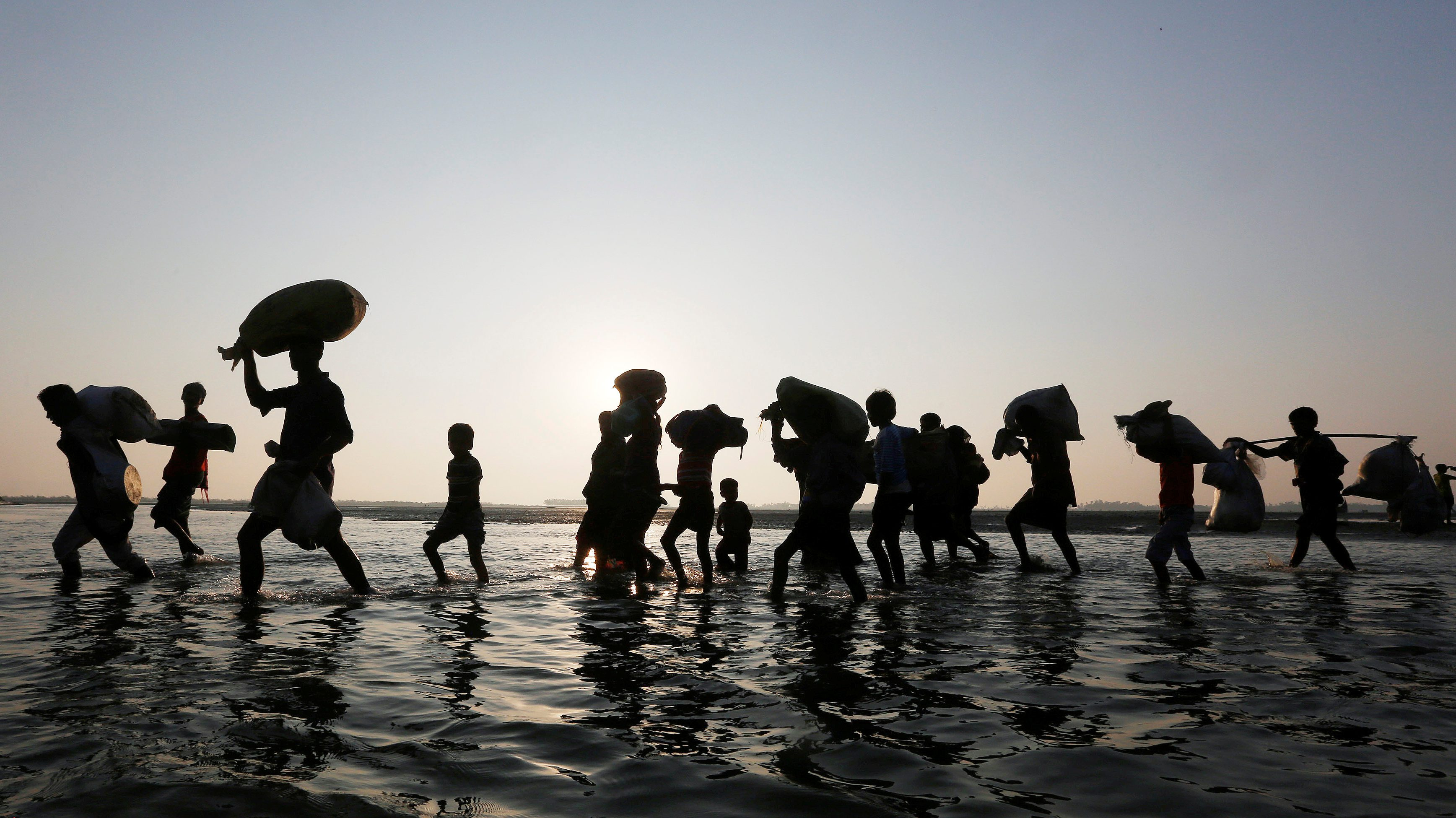 Rohingya refugees walk through water after crossing the Bangladesh-Myanmar border, at a port in Teknaf. Estimates vary, but the consensus is that there will be at least 200 million people displaced by climate change by 2050.