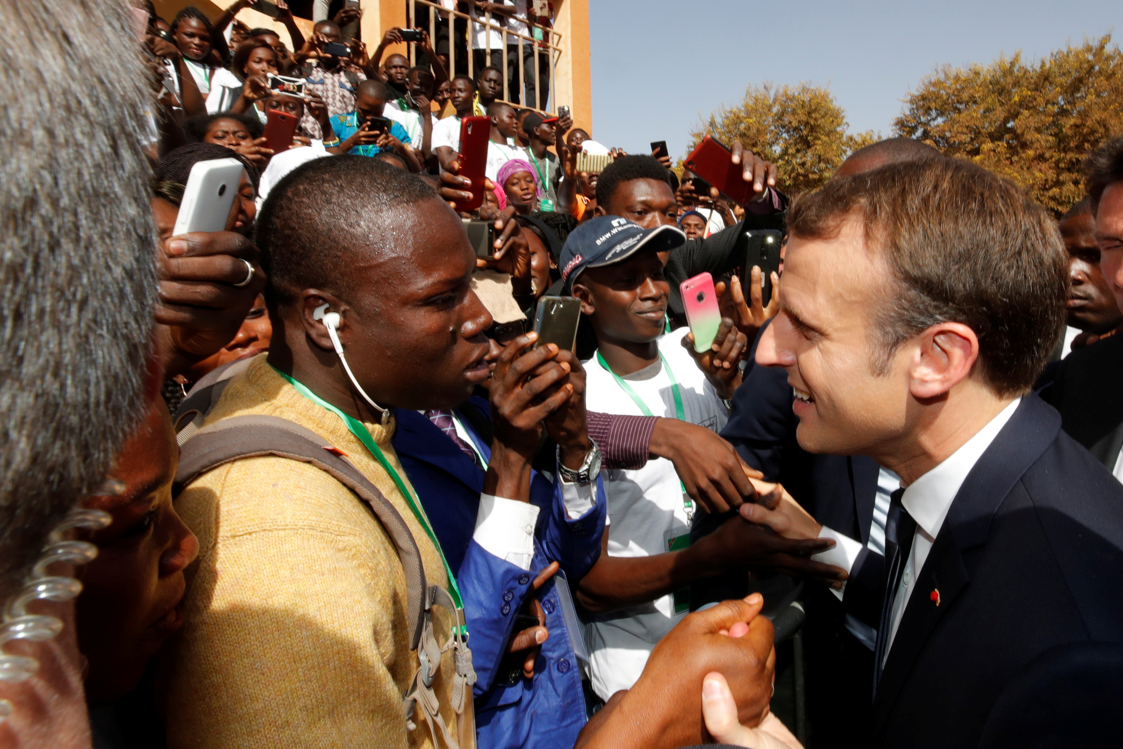 French President Emmanuel Macron shakes hands with people in the crowd as he leaves Ouagadougou University