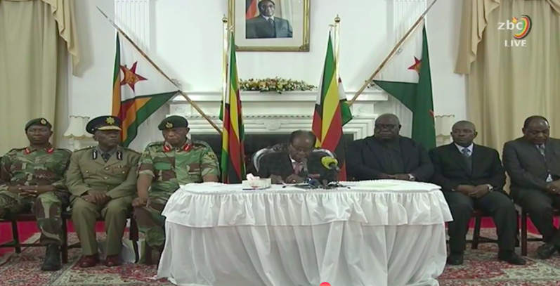 Robert Mugabe gives a statement in Harare, surrounded by senior military officials.