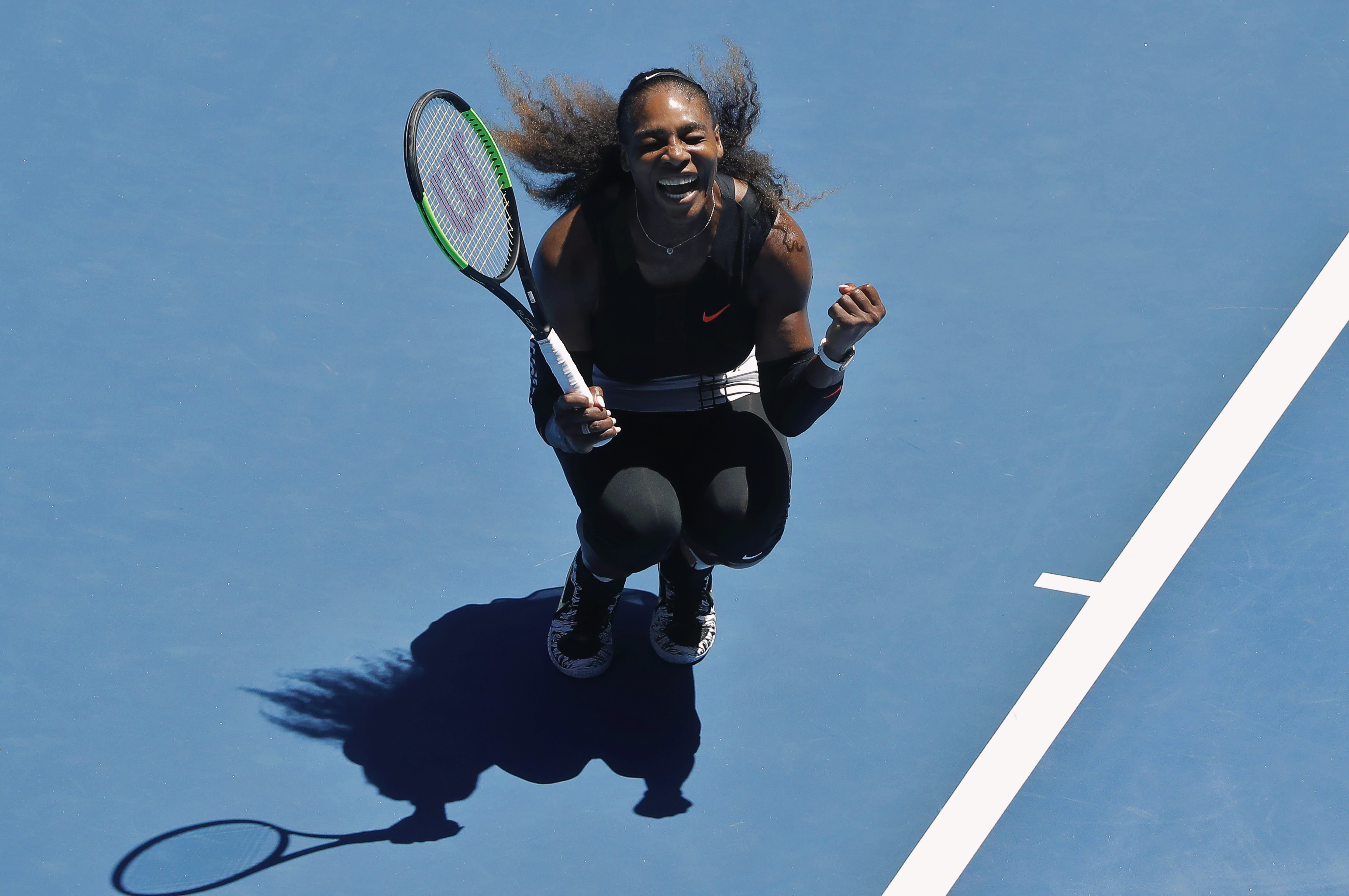 Serena Williams clenches fists in victory.