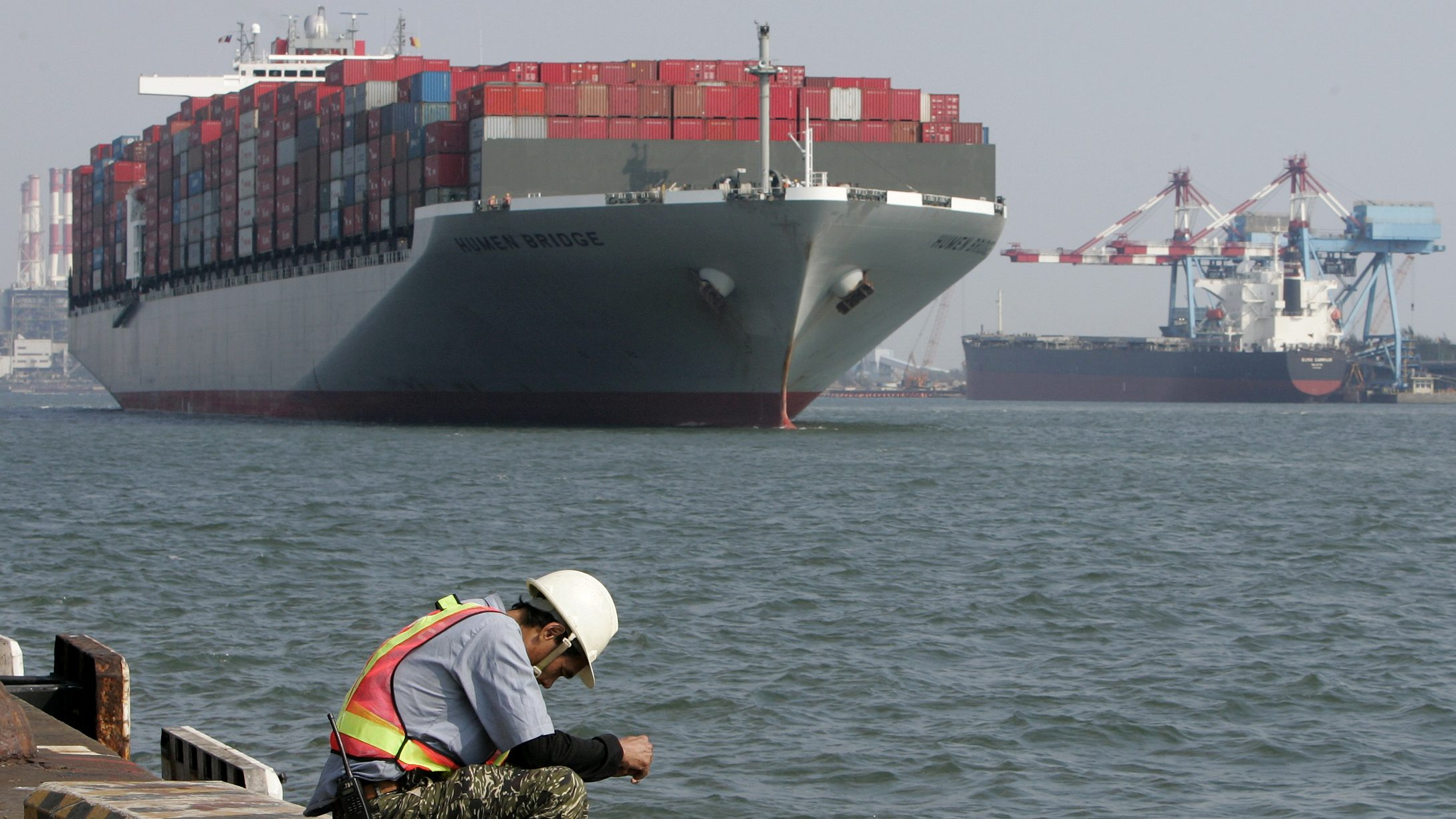 A man sits at the wharf of the Port of Kaohsiung in southern Taiwan May 12, 2009. Three major Chinese shipping companies plan to invest in the biggest Taiwanese port in Kaohsiung, a top port official said on Tuesday, as China and Taiwan forge closer trade ties. REUTERS/Pichi Chuang (TAIWAN BUSINESS) - GM1E55C1HIO01