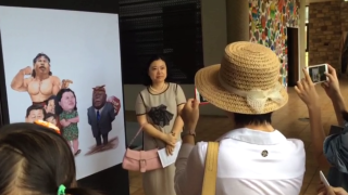 Sun Baohong, China's ambassador poses in-front of one Ackwerh's cartoons which satirizes Chinese threats