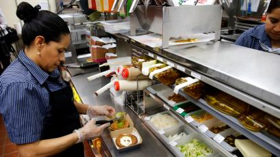 In this Thursday, June 1, 2017, photo, Silvia Ruiz prepares a specialty sandwich at a McDonald's restaurant in Chicago.