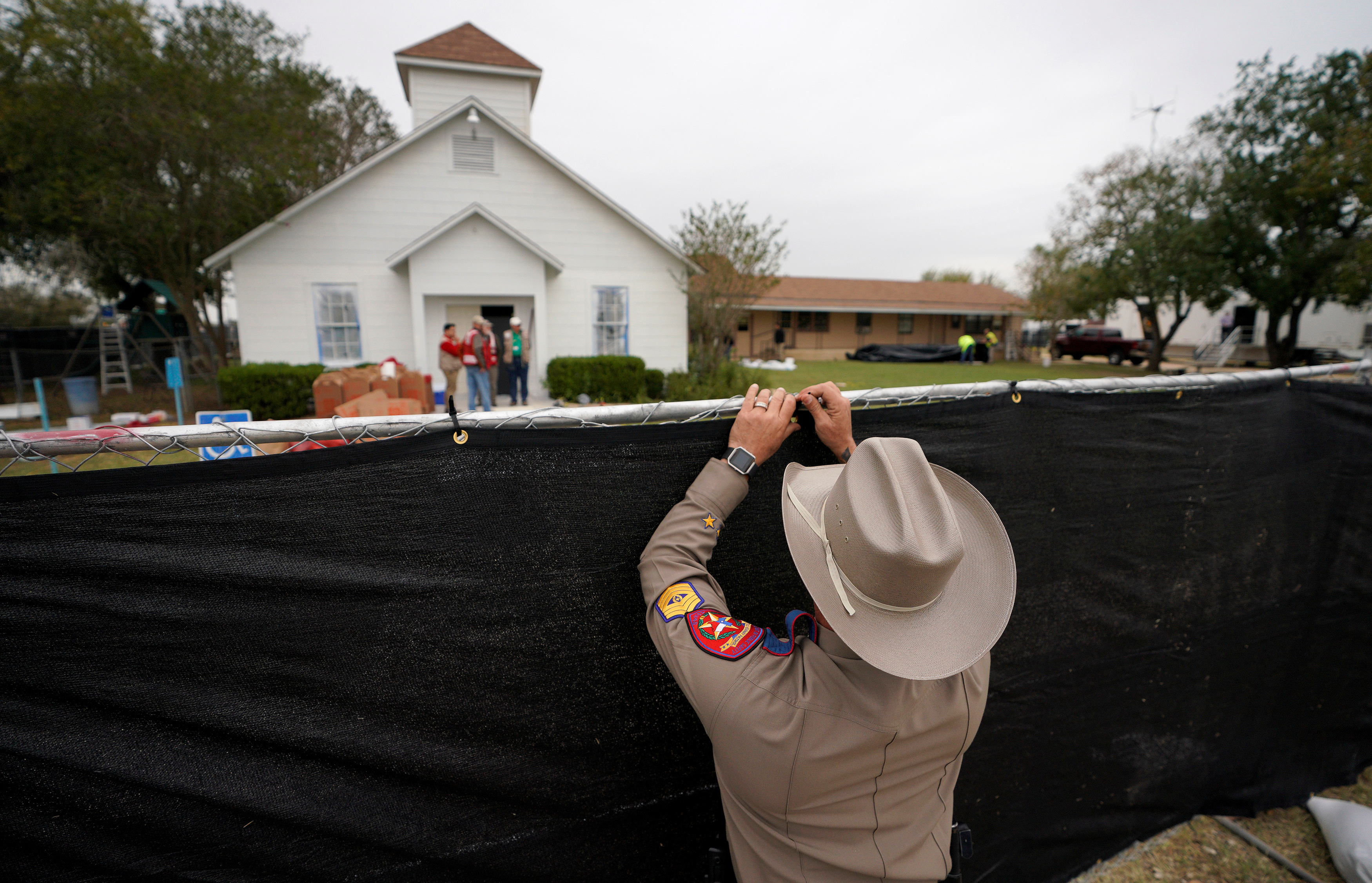 A Texas state trooper helps erect a fence around the site of the shooting at the First Baptist Church of Sutherland Springs