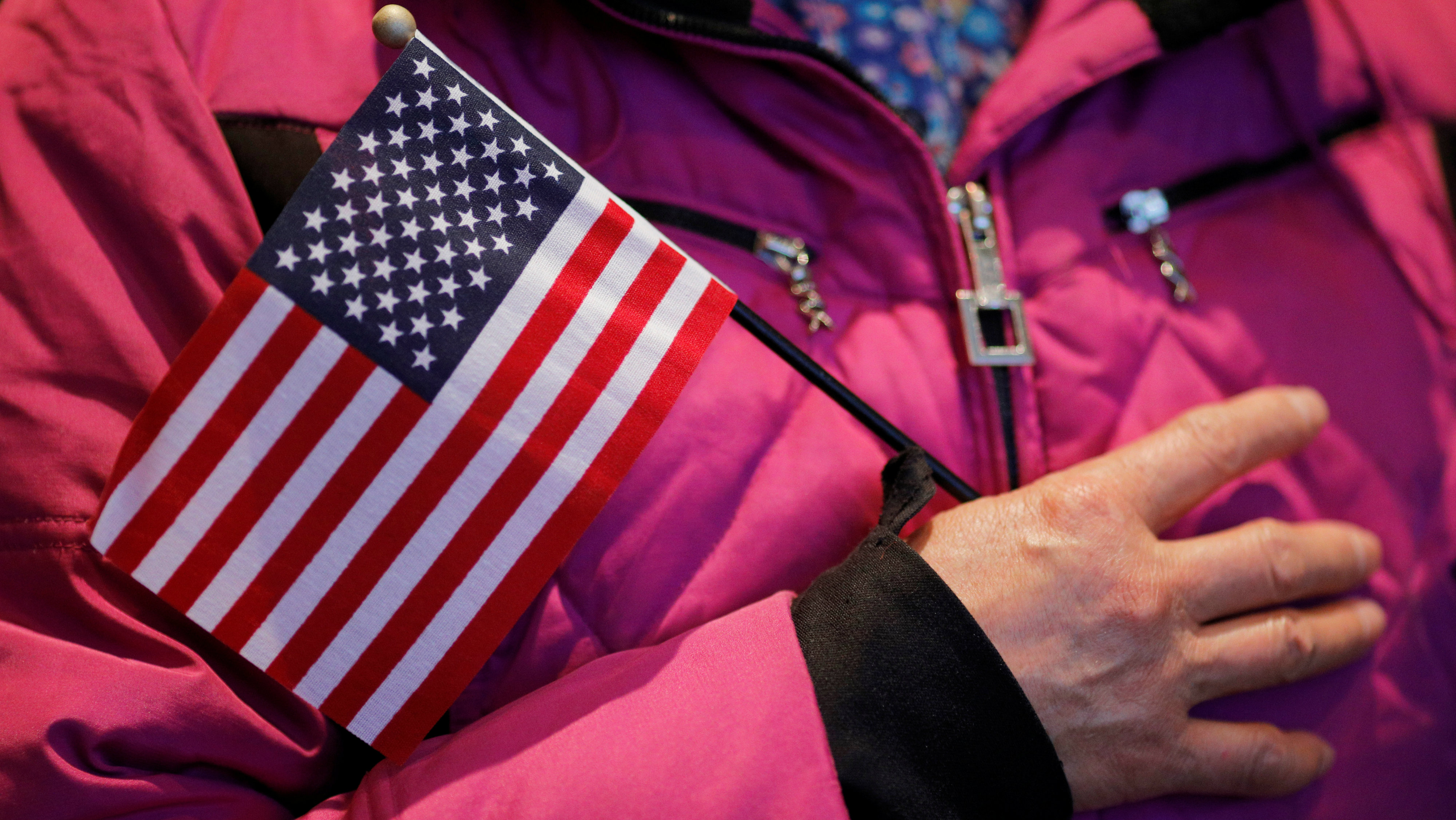 Seventy-three year-old Dianrong Wang of China holds a U.S. flag as the National Anthem is sung during a citizenship ceremony at the John F. Kennedy Presidential Library in Boston, Massachusetts, U.S. February 8, 2017.