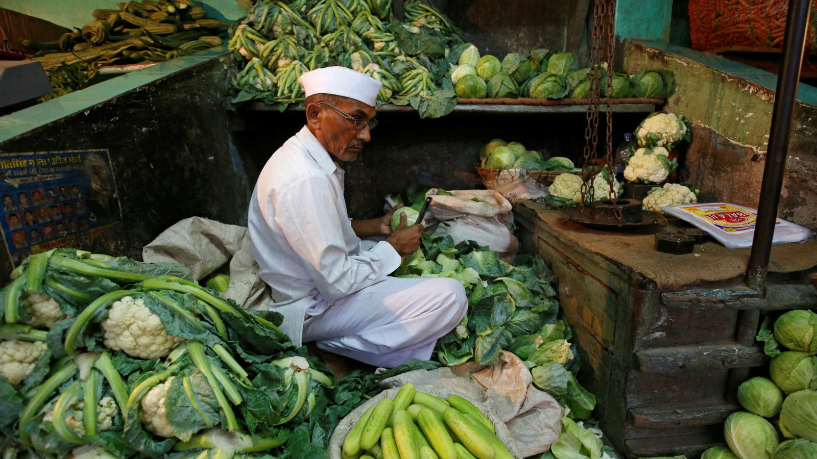 A vendor works at his stall as he waits for customers at a wholesale fruit and vegetable market in Mumbai...