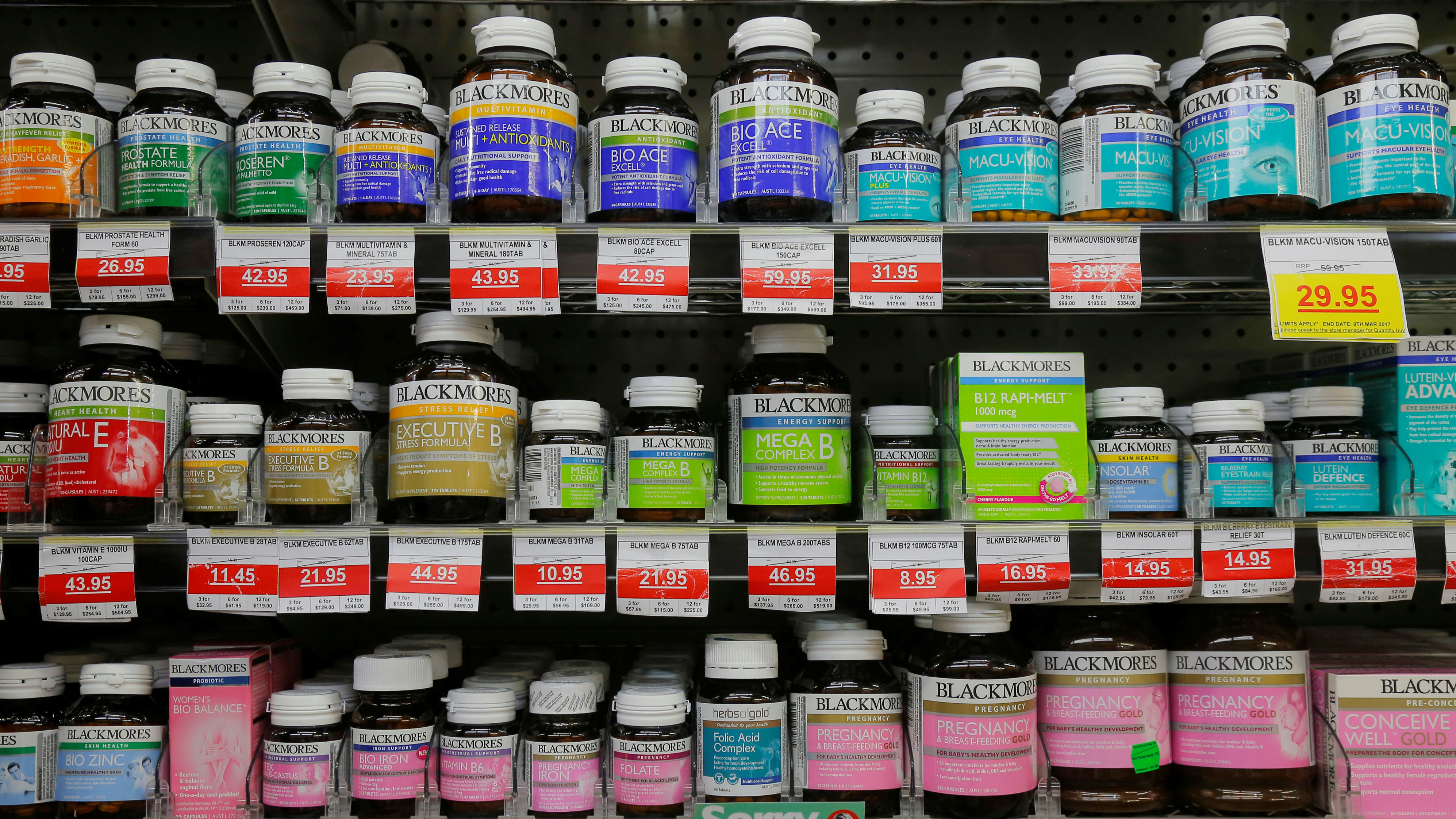 Rows and rows of vitamins and supplements on a pharmacy shop shelf.