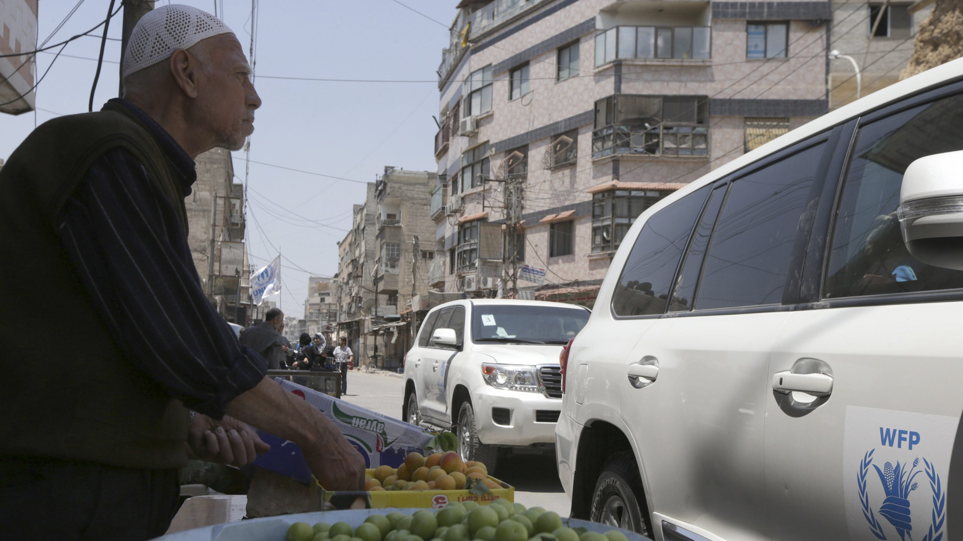 A fruit vendor stands beside passing World Food Program vehicles in eastern Ghouta of Damascus, May 24, 2014. A delegation from the United Nations, the World Food Program, UNICEF and the World Health Organization, accompanied by the Syrian Red Crescent, visited the eastern Damascus suburb of Ghouta carrying humanitarian aid to be distributed to the residents, and moved in the area accompanied by the Free Syrian Army, activists said.