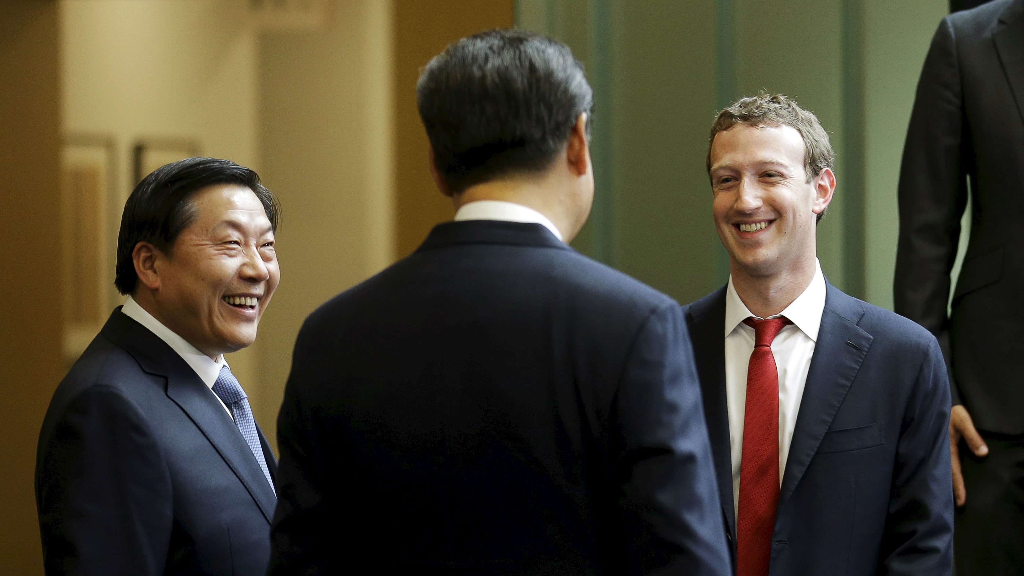 Chinese President Xi Jinping (C) talks with Facebook Chief Executive Mark Zuckerberg (R) as China's top Internet regulator Lu Wei (L) looks on, during a gathering of CEOs and other executives at Microsoft's main campus in Redmond, Washington